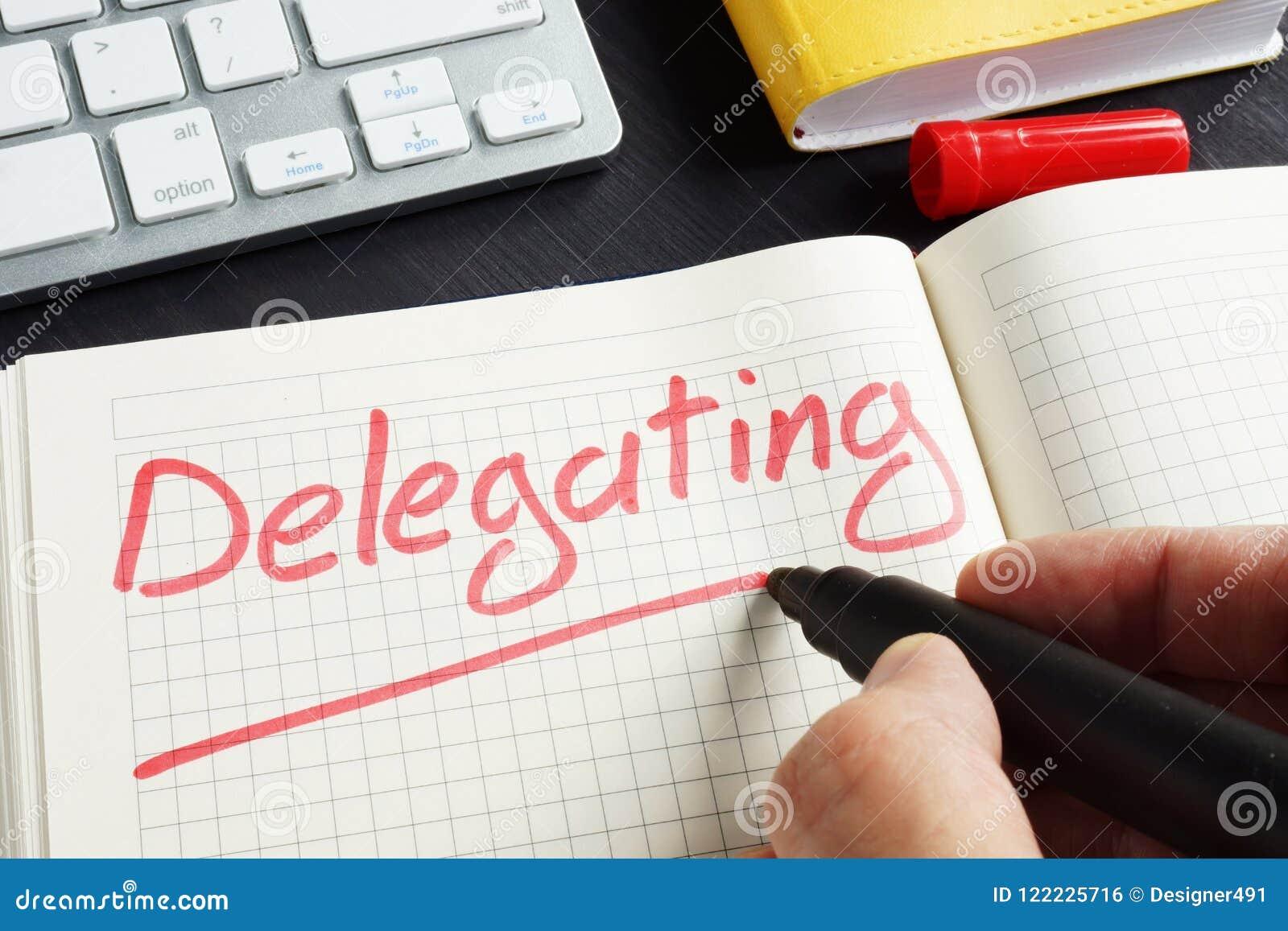 El hombre está escribiendo la delegación en la libreta Concepto del delegado