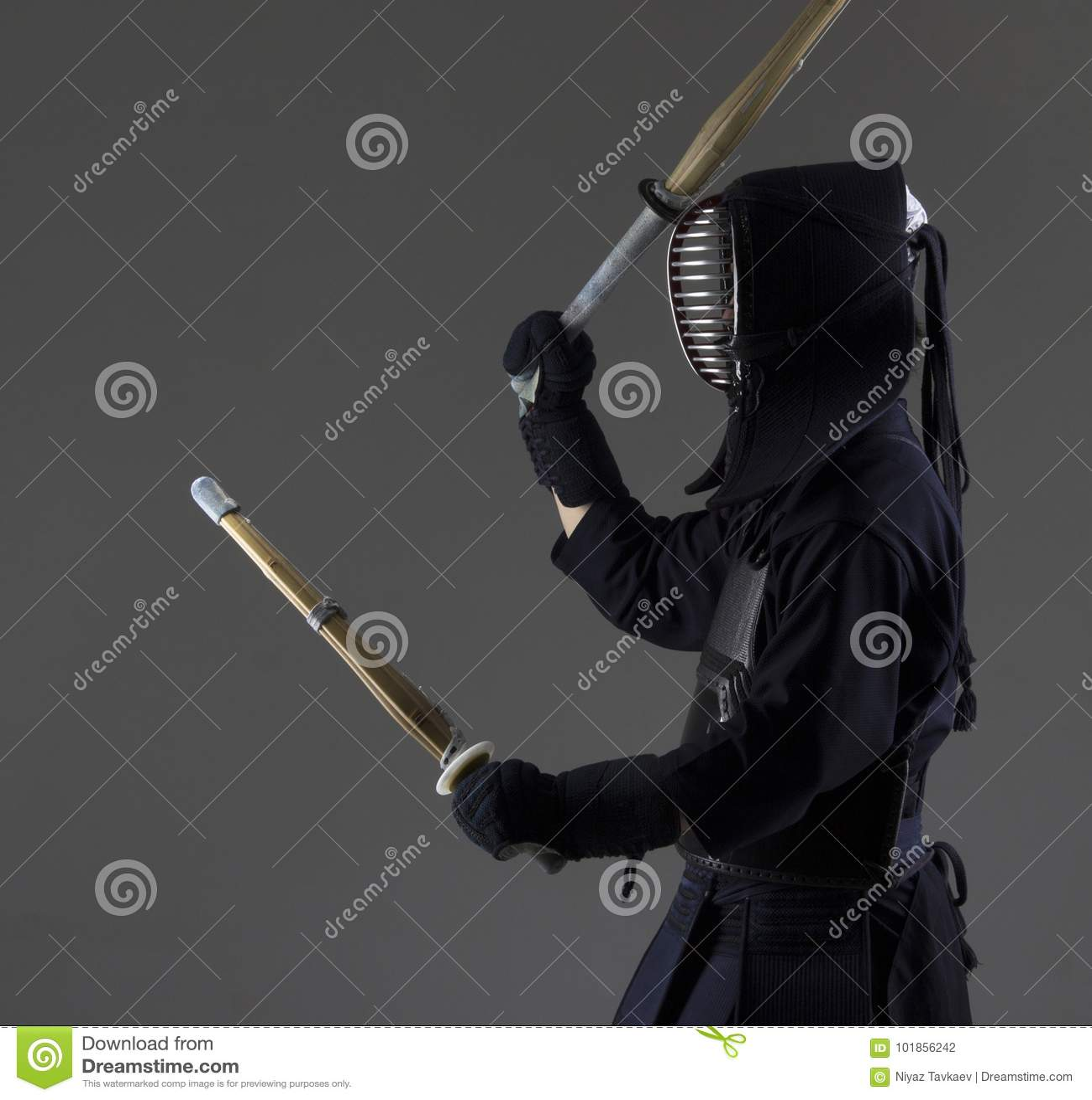 El hombre está practicando kendo en armadura tradicional Él que balancea con dos espadas de bambú