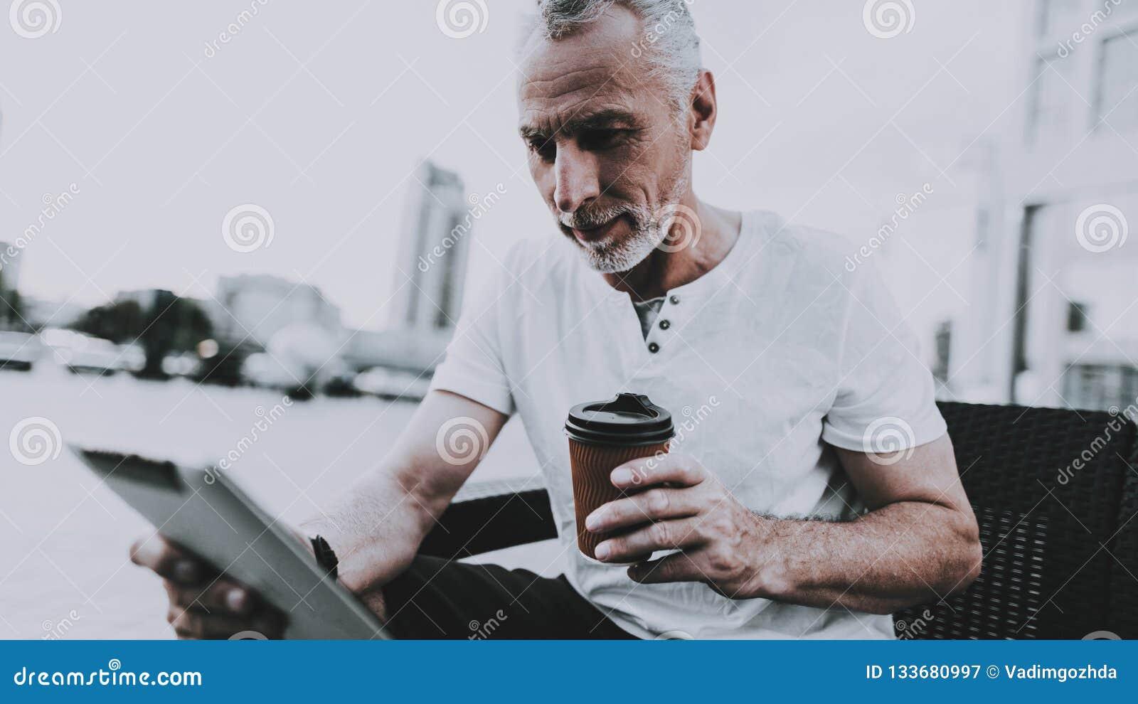 El hombre está utilizando un Tablet PC y está bebiendo un café