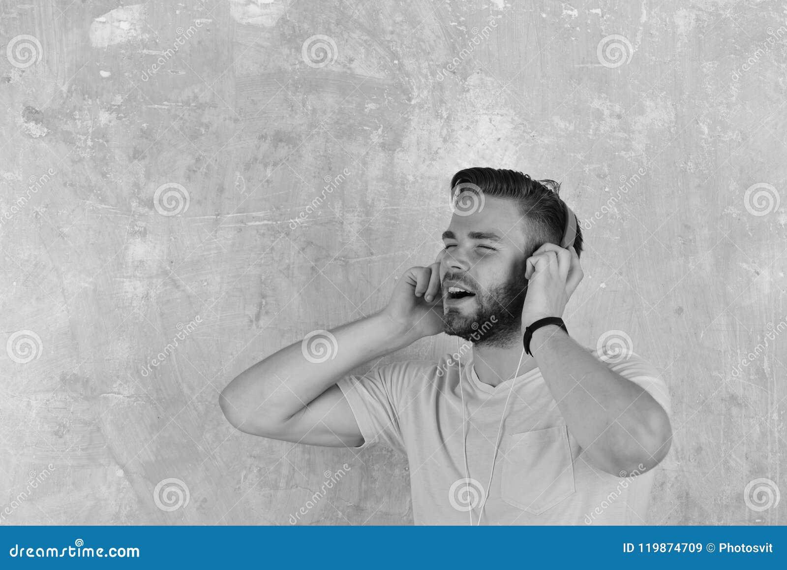 El hombre europeo tiene tiempo de la diversión Individuo barbudo hermoso americano con los auriculares