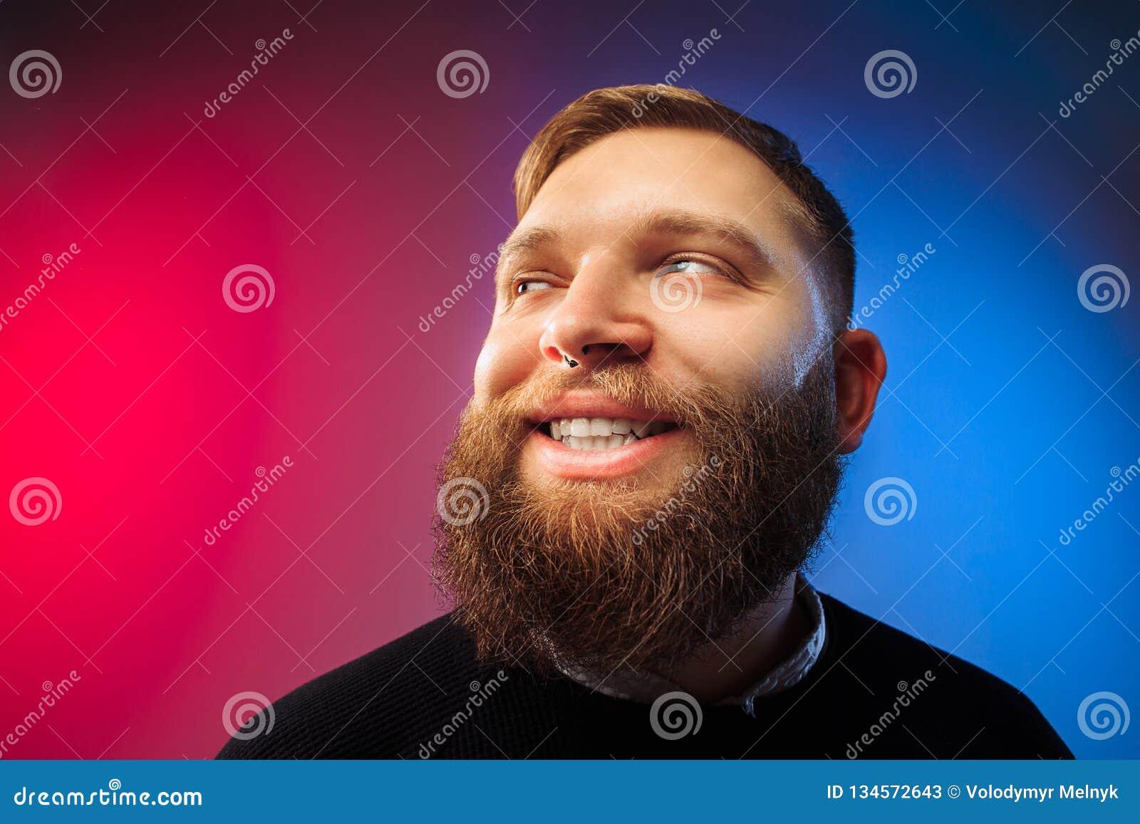 El hombre feliz que se opone y que sonríe contra fondo rosado