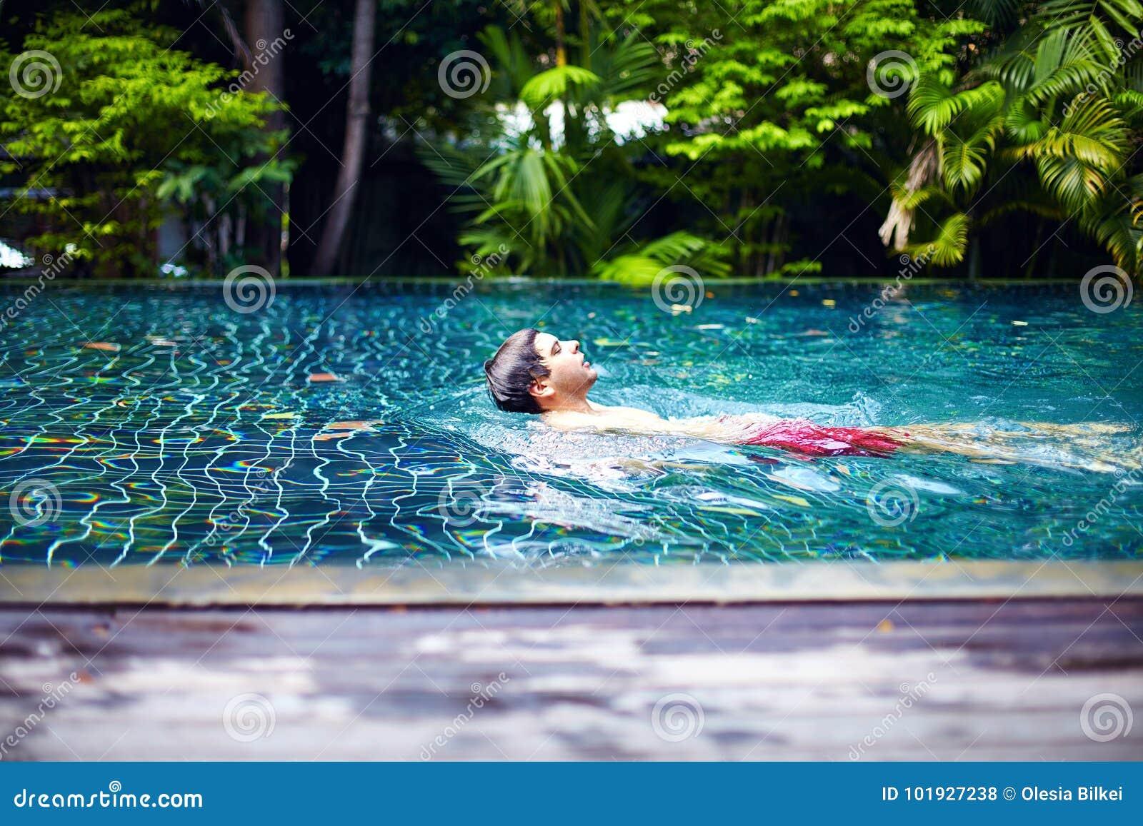 El hombre goza el nadar en piscina en el escape reservado de la partida