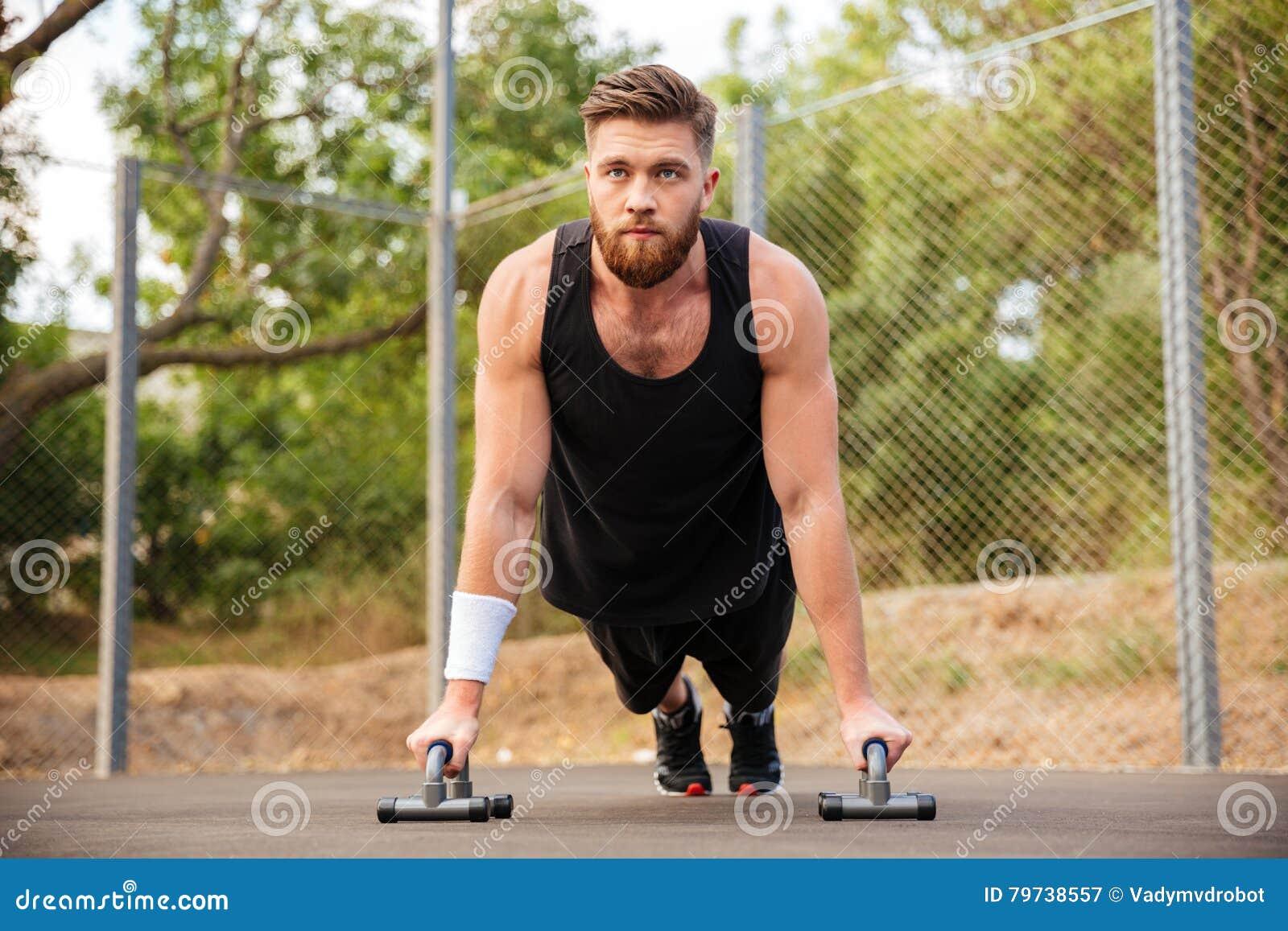 El hombre hermoso de la aptitud que hace el pectoral ejercita con el equipo de deporte