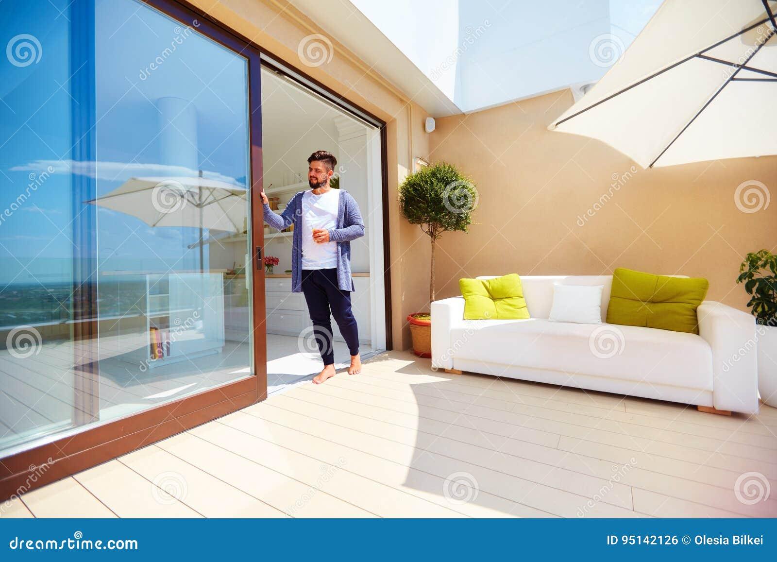 El hombre hermoso disfruta de vida en terraza del tejado, con la cocina del espacio abierto y las puertas deslizantes