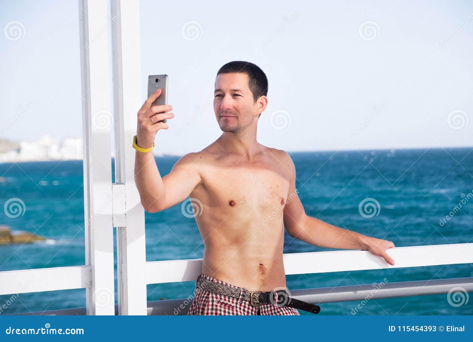 El hombre hermoso hace el selfie usando smartphone Verano, torso