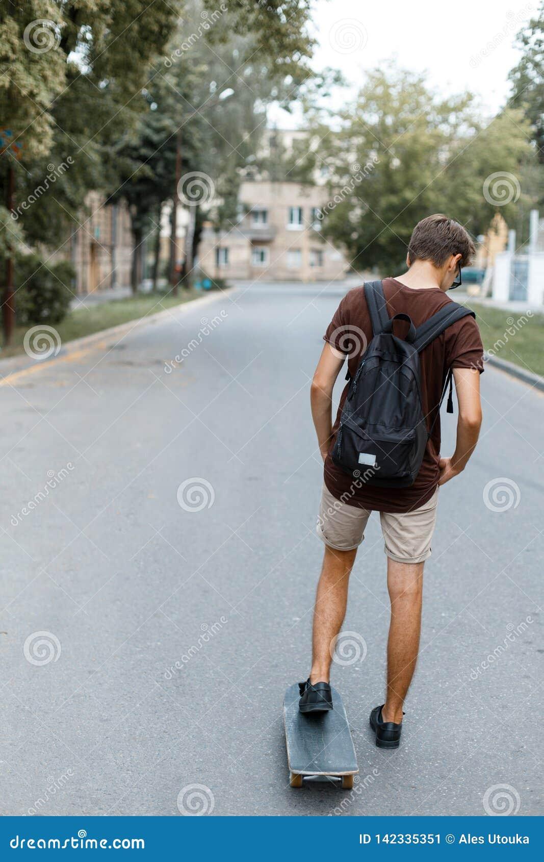 El hombre hermoso joven atlético del inconformista en ropa de moda del verano con una mochila negra monta snowboard Individuo de
