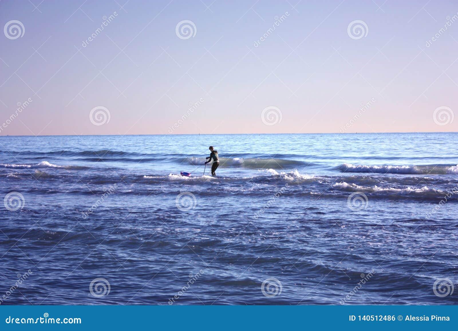 El hombre hundió en la pesca en mar y recoge tellines o las almejas u otros mariscos en un día de invierno