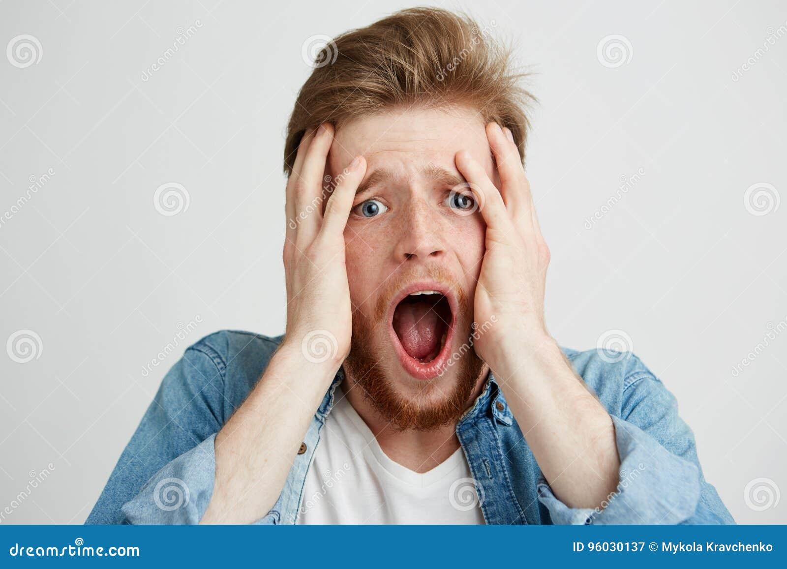 El hombre joven asustado del trastorno triste que mira la cámara con la boca abierta que se sostiene principal con entrega el fon