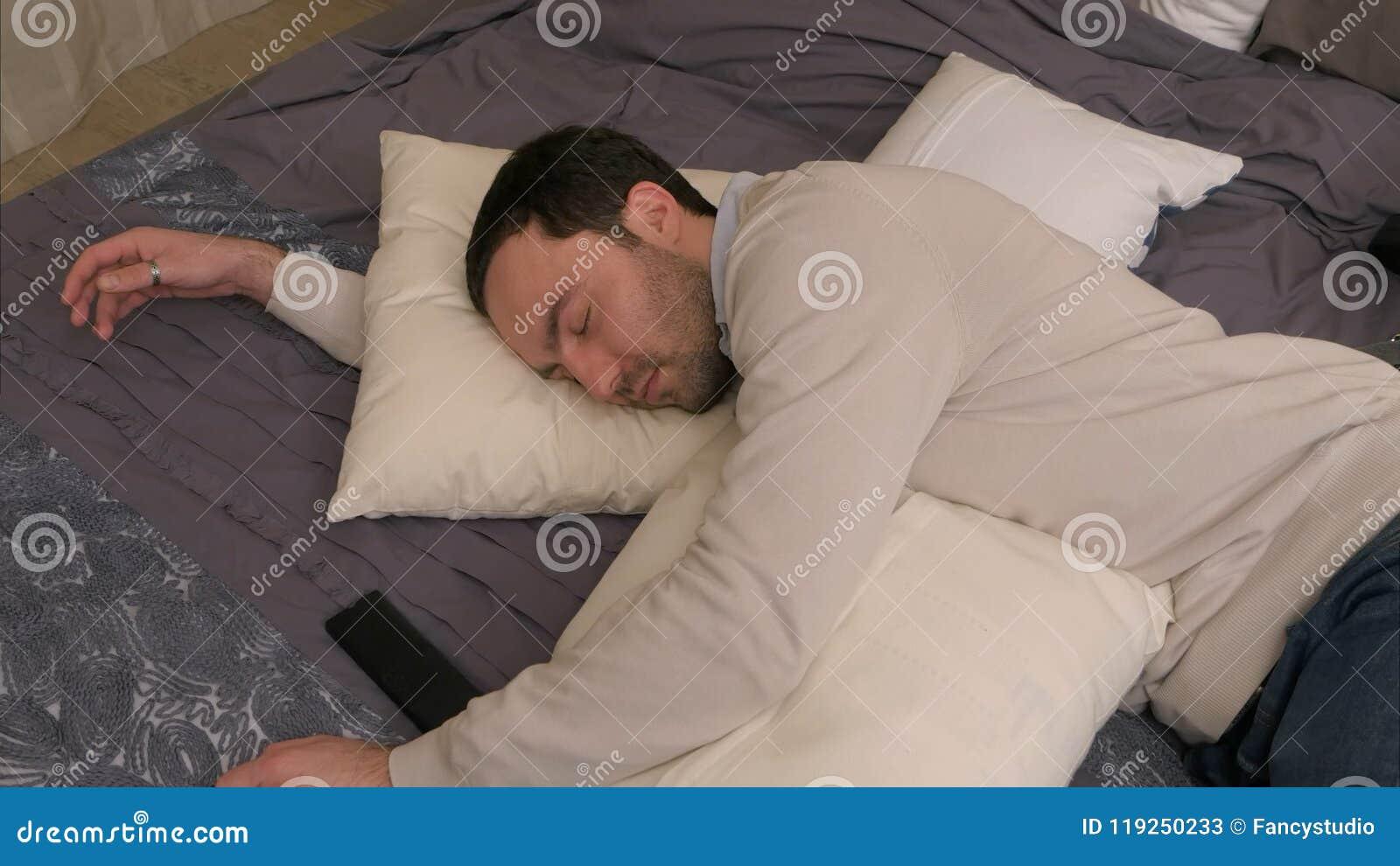 El hombre joven cansado miente en cama y se cae dormido después de día laborable duro