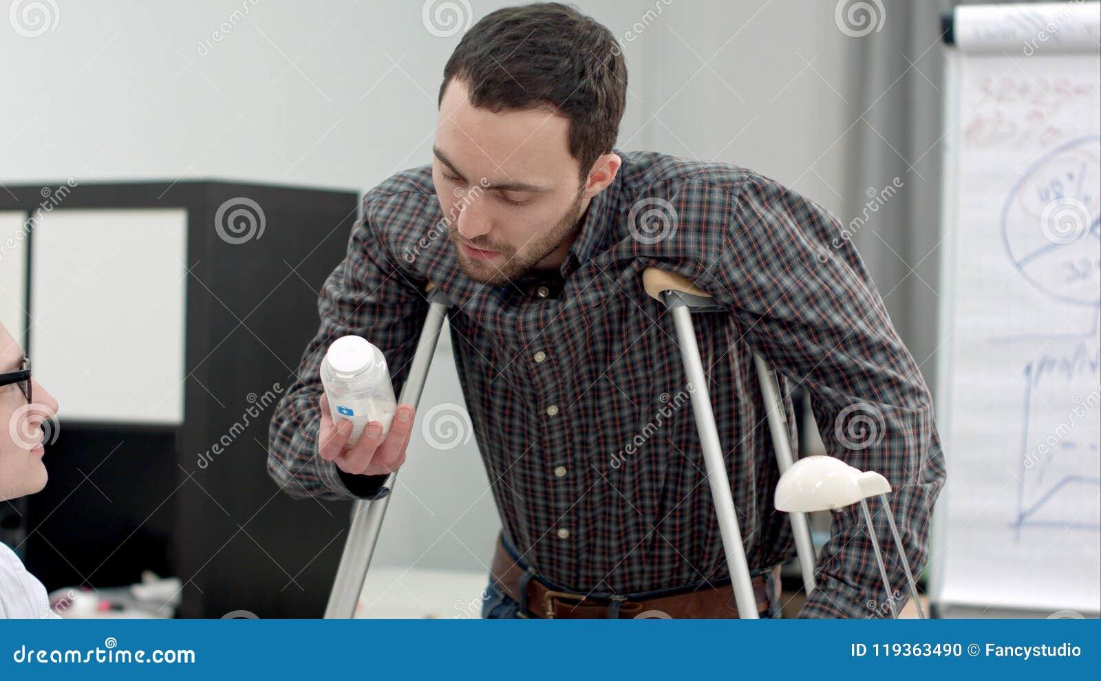 El hombre joven con las muletas que miraban píldoras prescribió por el doctor