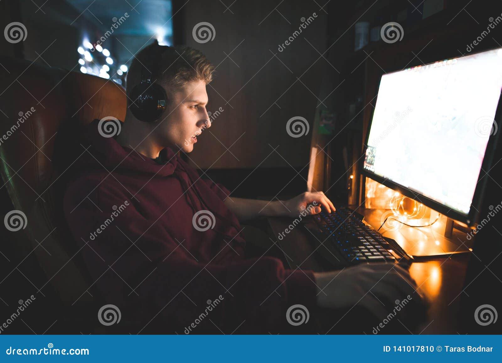 El hombre joven concentrado atractivo sienta el hogar en un cuarto acogedor y trabajos en un ordenador