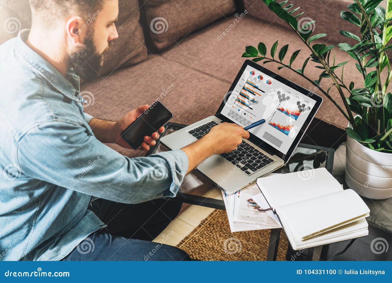 El hombre joven del inconformista, empresario se sienta en casa en el sofá en la mesa de centro, sosteniendo el smartphone, mostr