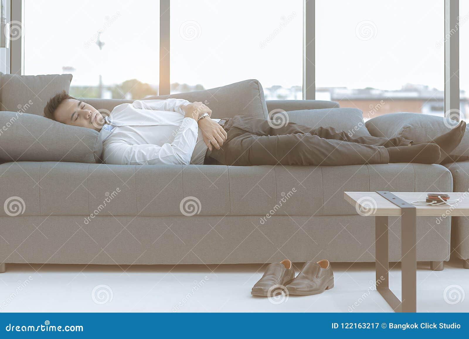El hombre joven dormía en un sofá grande comfortablemente en luxur