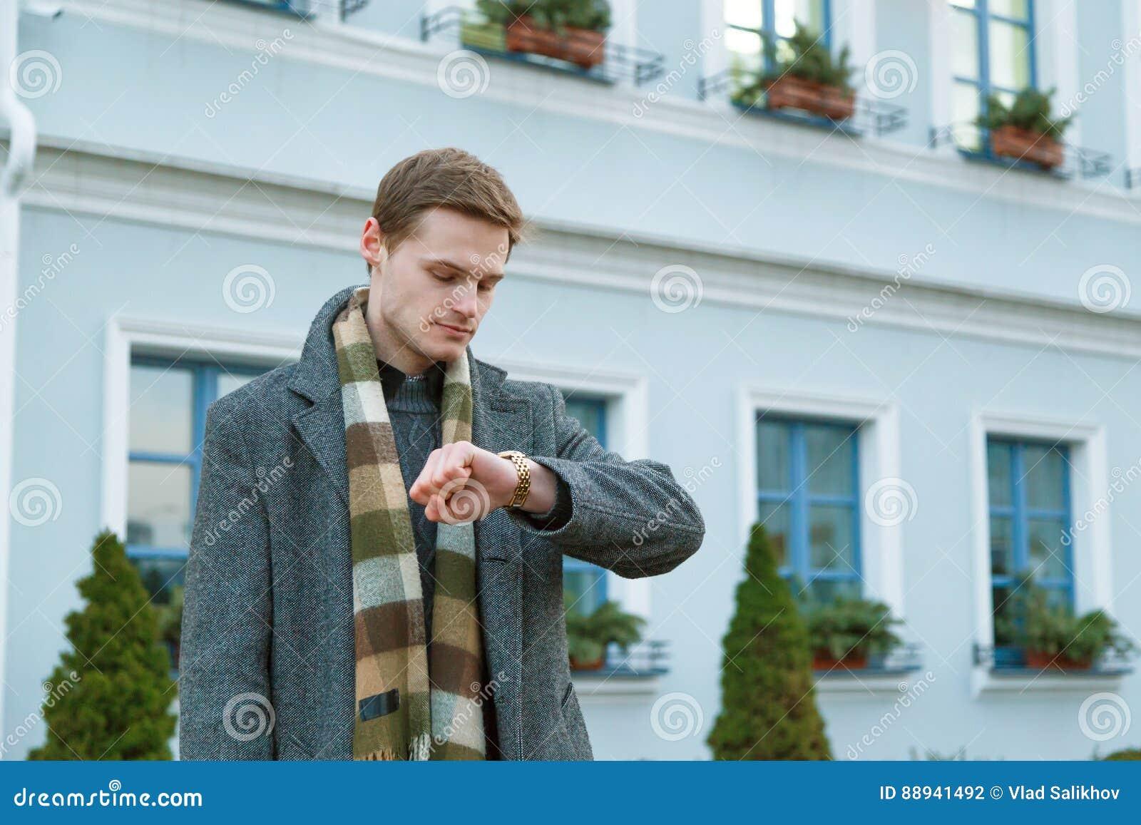 El hombre joven en capa está mirando su reloj mientras que se coloca al aire libre en la ciudad Concepto de la cita del tiempo