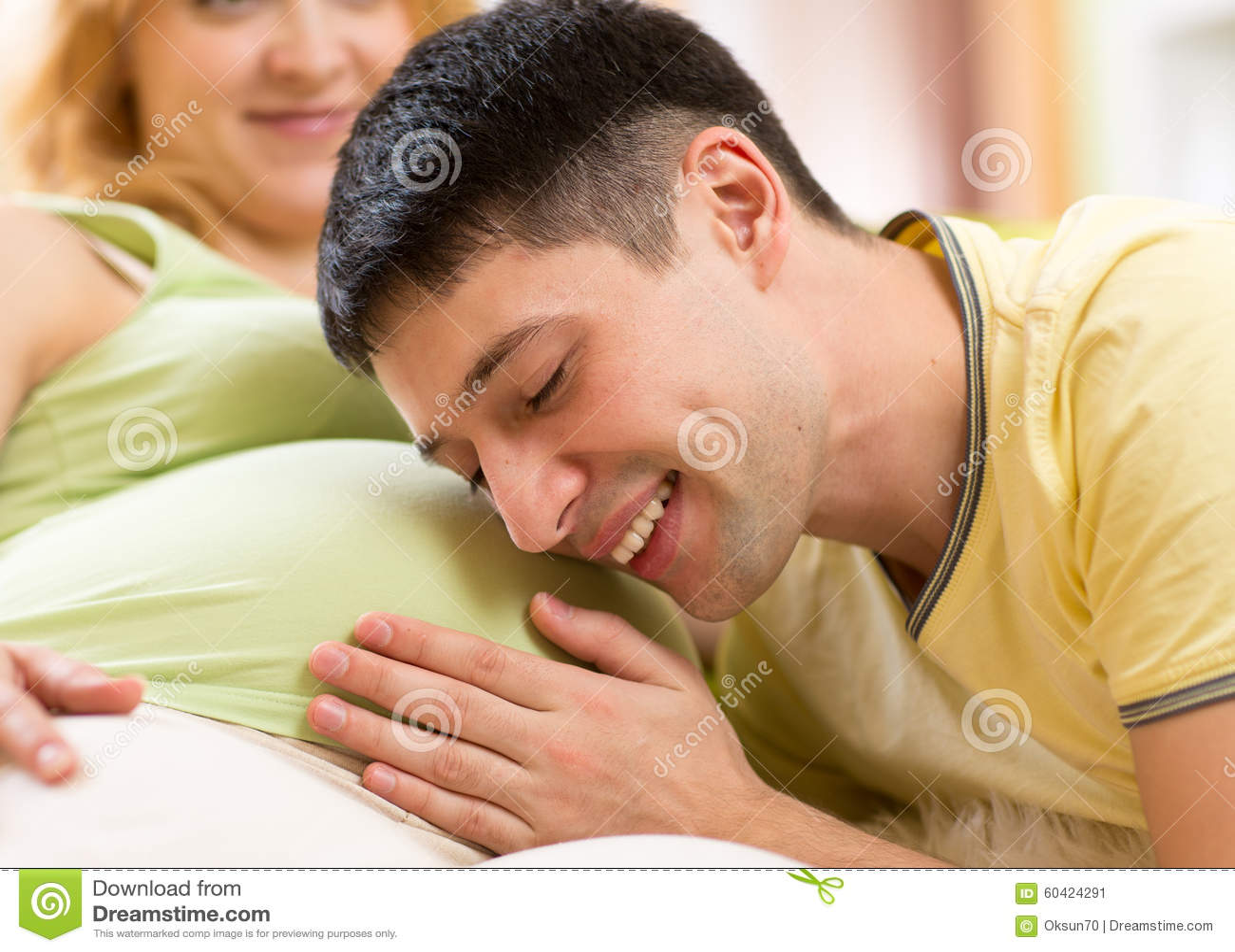 El hombre joven frota ligeramente la panza de su mujer embarazada