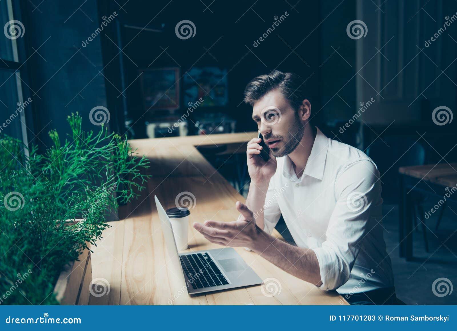 El hombre joven hermoso confiado está teniendo una conversación del negocio,