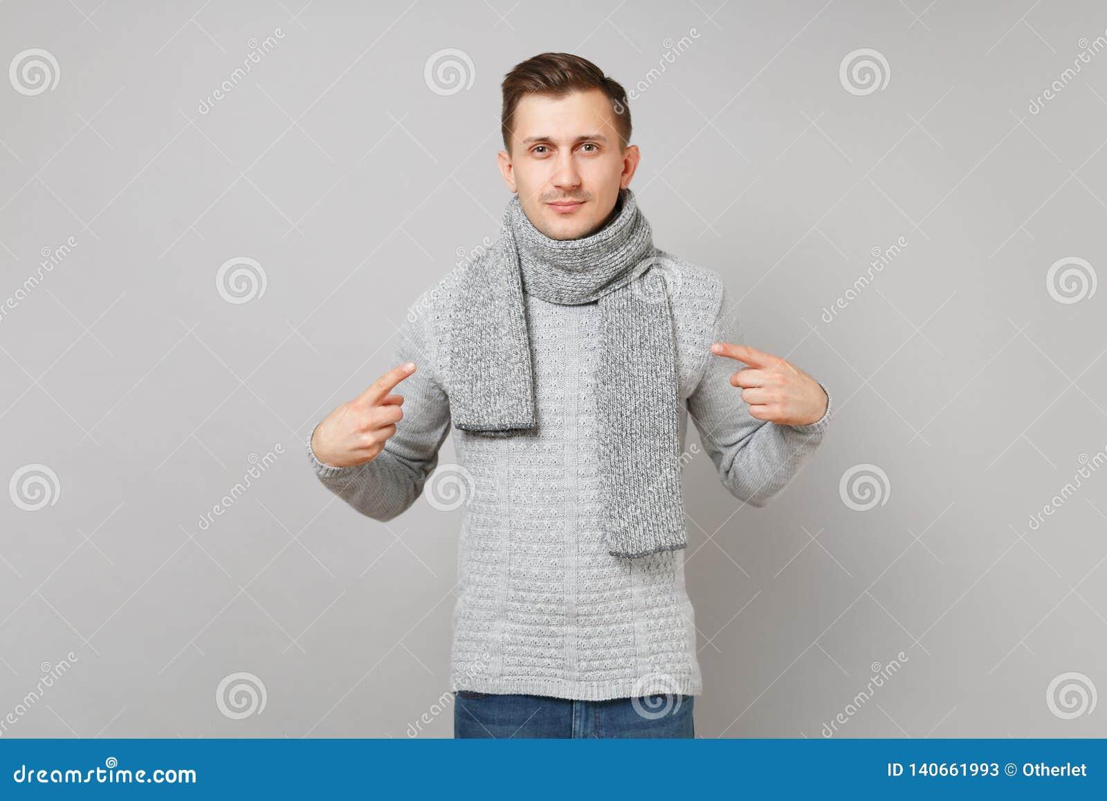 El hombre joven hermoso en el suéter gris, bufanda señalando los dedos índices en sí mismo aisló en fondo gris de la pared Sano