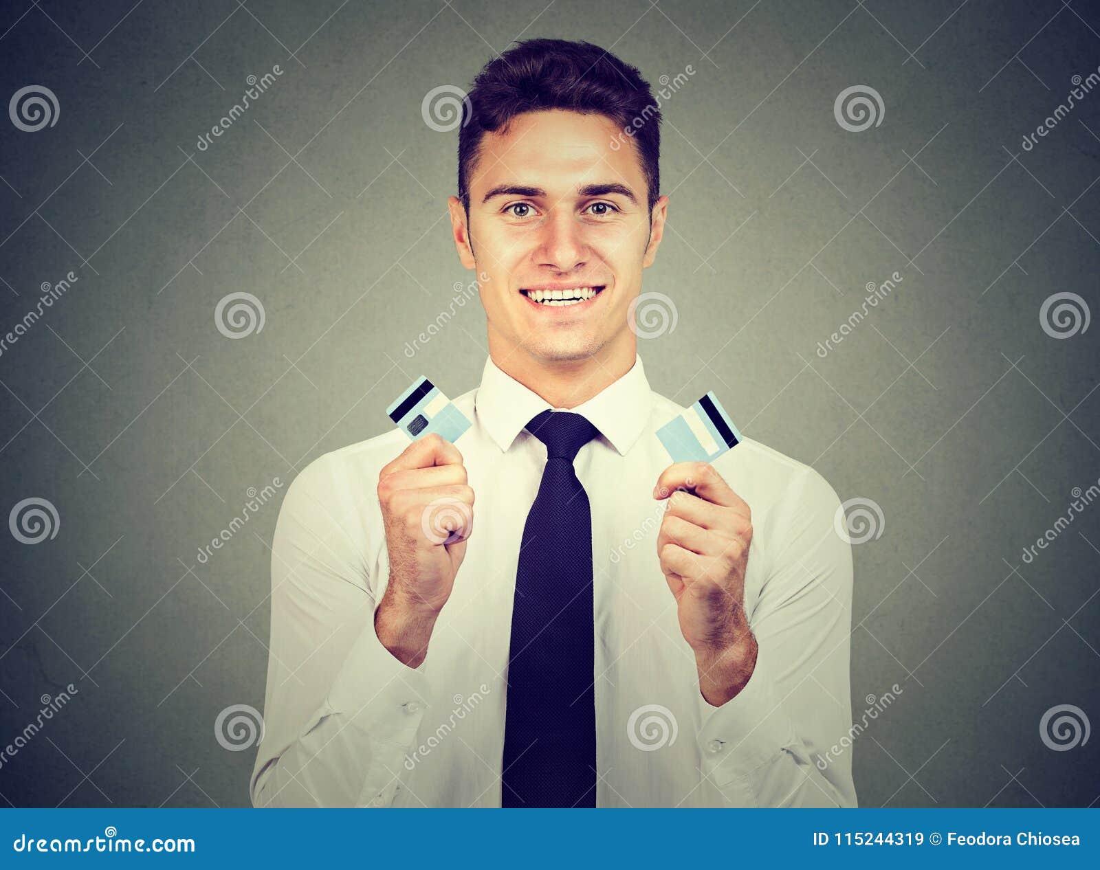 El hombre joven libre de la deuda feliz que sostenía una tarjeta de crédito cortó en dos pedazos