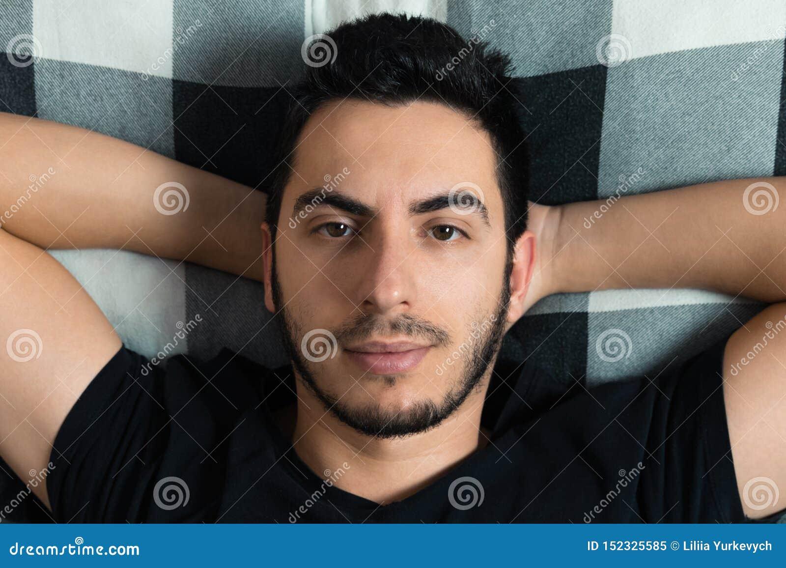 El hombre joven miente en cama