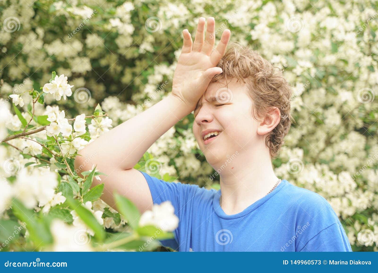 El hombre joven se coloca entre las flores y disfruta de verano y de florecimiento