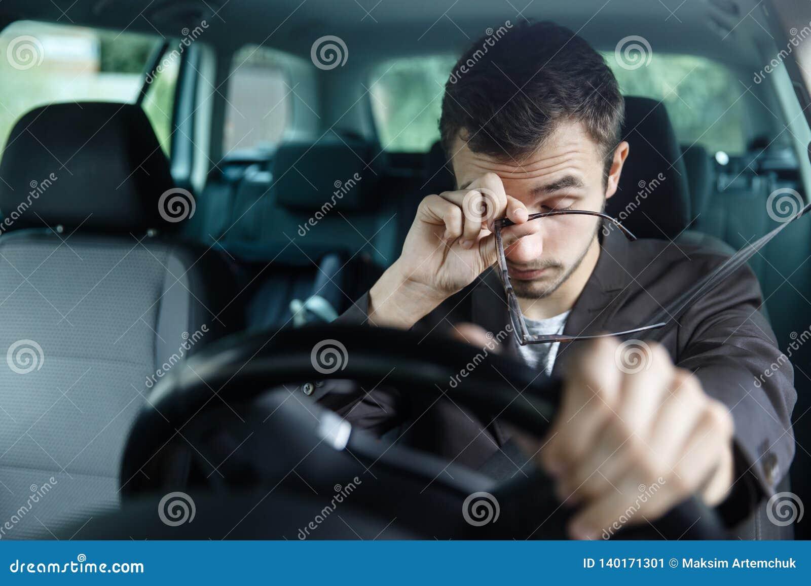 El hombre joven soñoliento frota sus ojos con su mano derecha Su mano izquierda está en el volante Él se está sentando en su coch