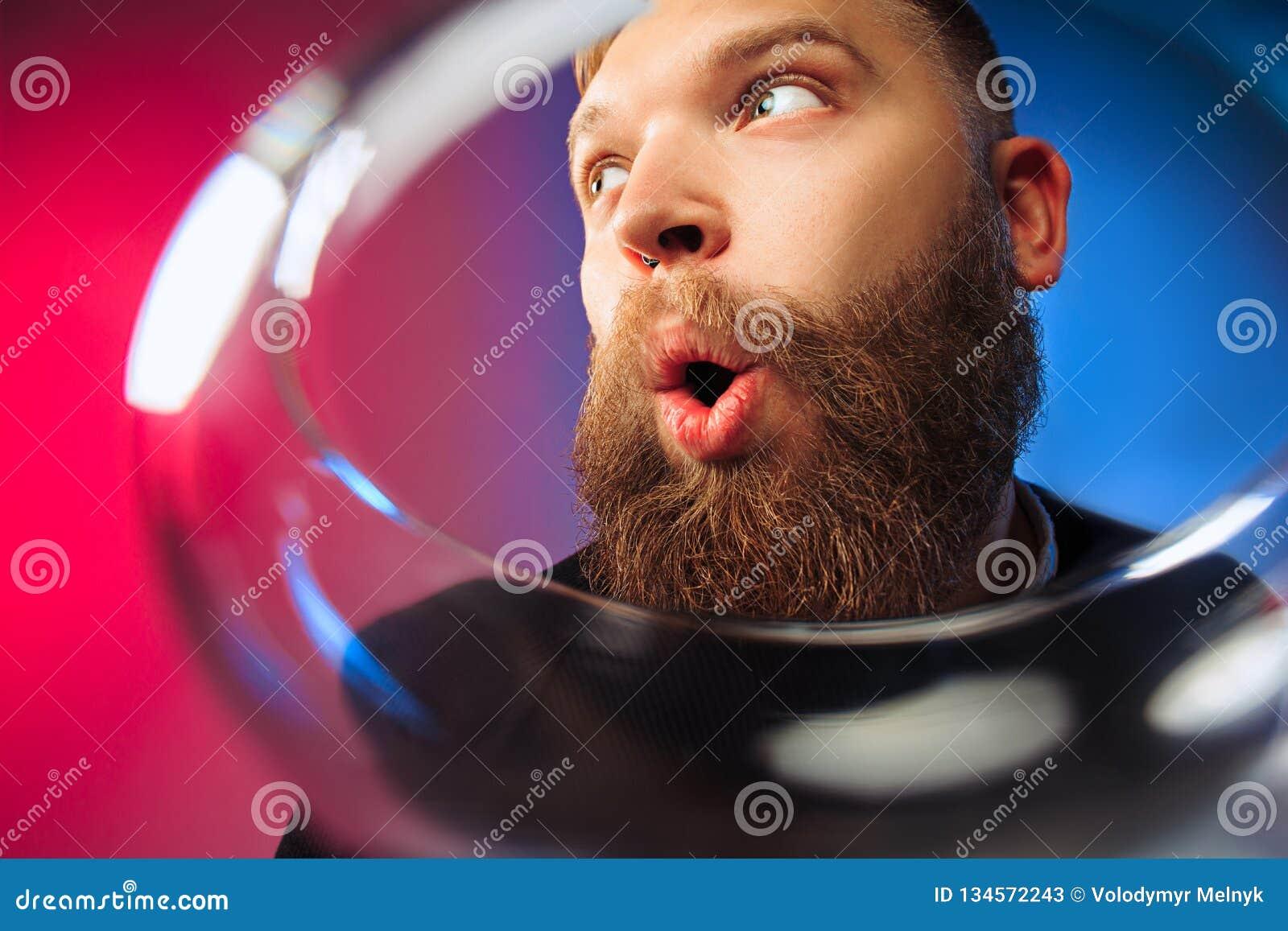 El hombre joven sorprendido que presenta con la copa de vino