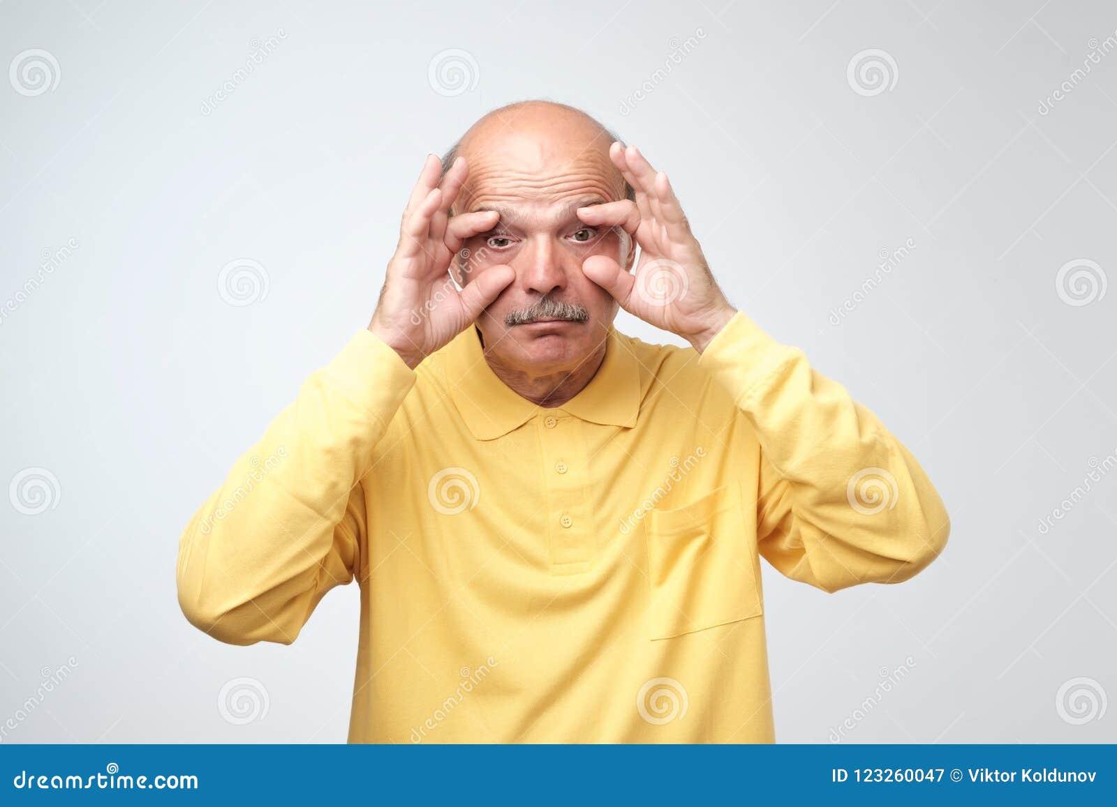 El hombre mayor soñoliento aburrido hermoso que intenta abrir el suyo observa con los fingeres