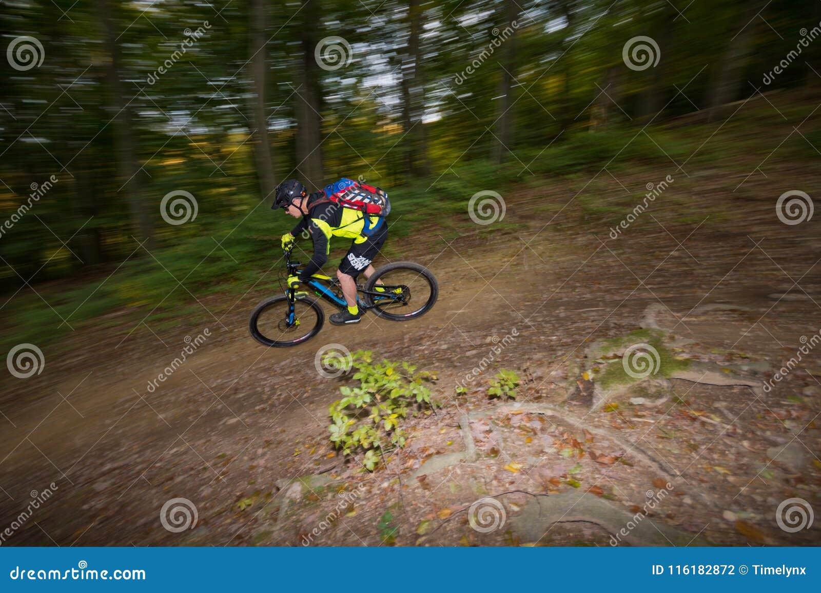 El hombre monta la e-bici cuesta abajo en rastro del bosque