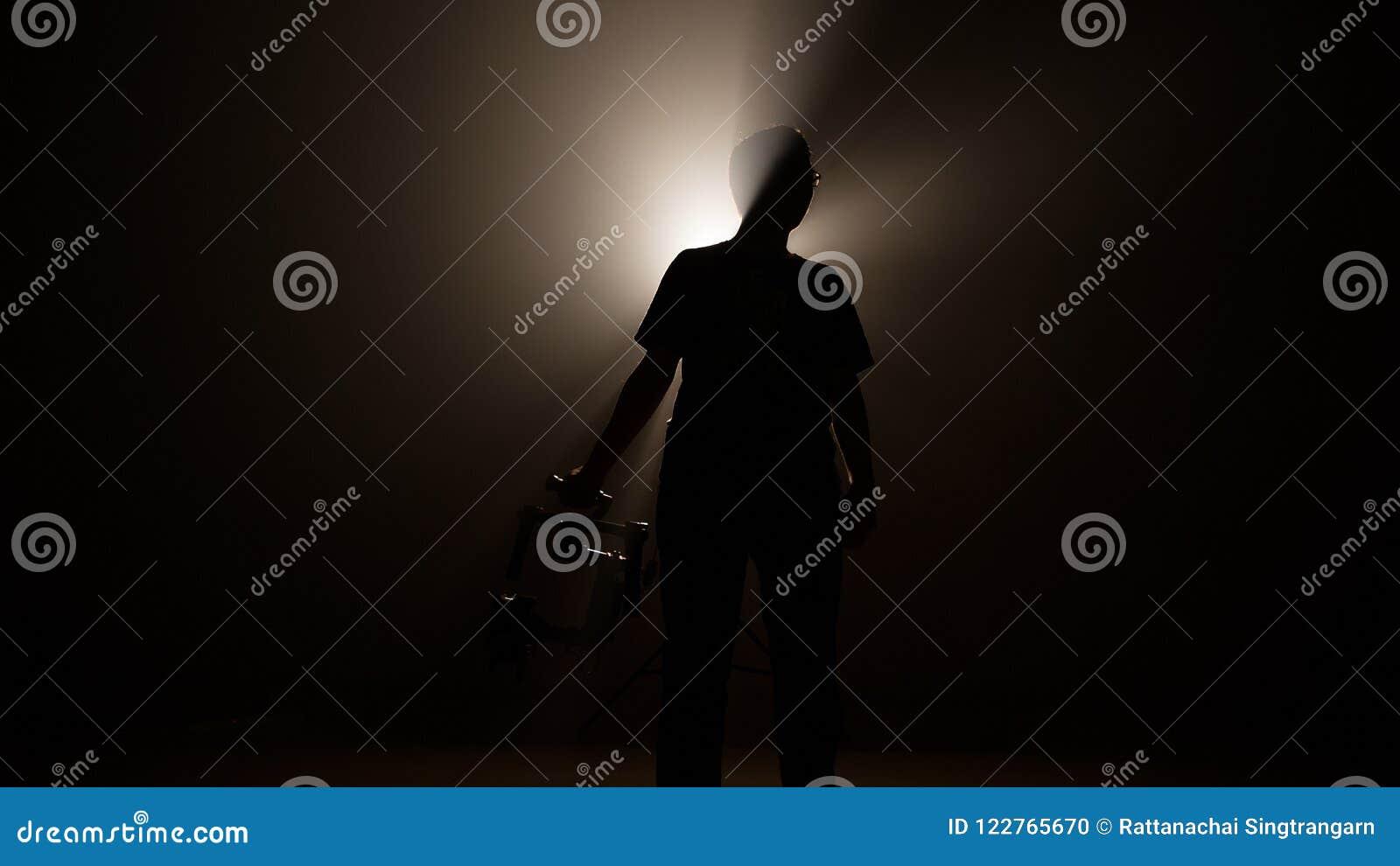El hombre profesional oscuro de la silueta lleva a cabo el ronin de la estabilidad para la producción video de la película y hace