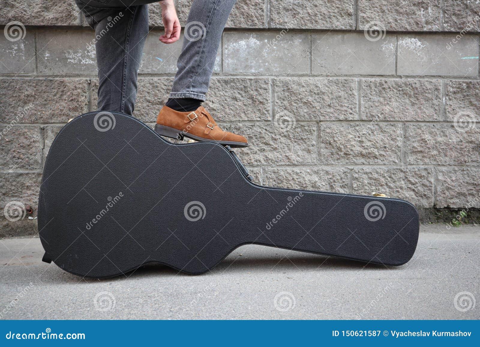 El hombre puso su pie en una caja dura de la guitarra Estuche r?gido para la guitarra el?ctrica Hombre vestido en los vaqueros qu