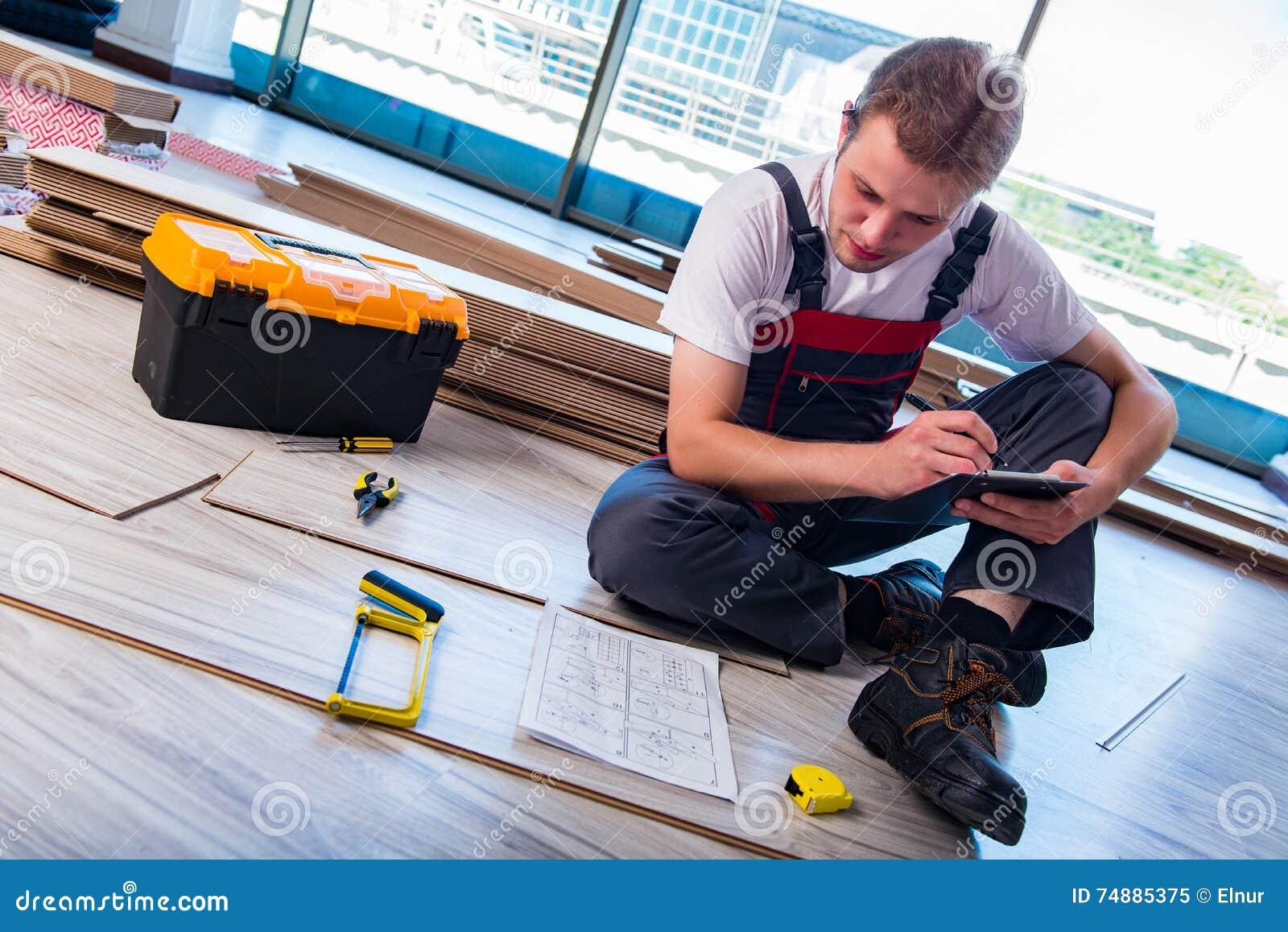 El hombre que pone el suelo laminado en concepto de la construcción
