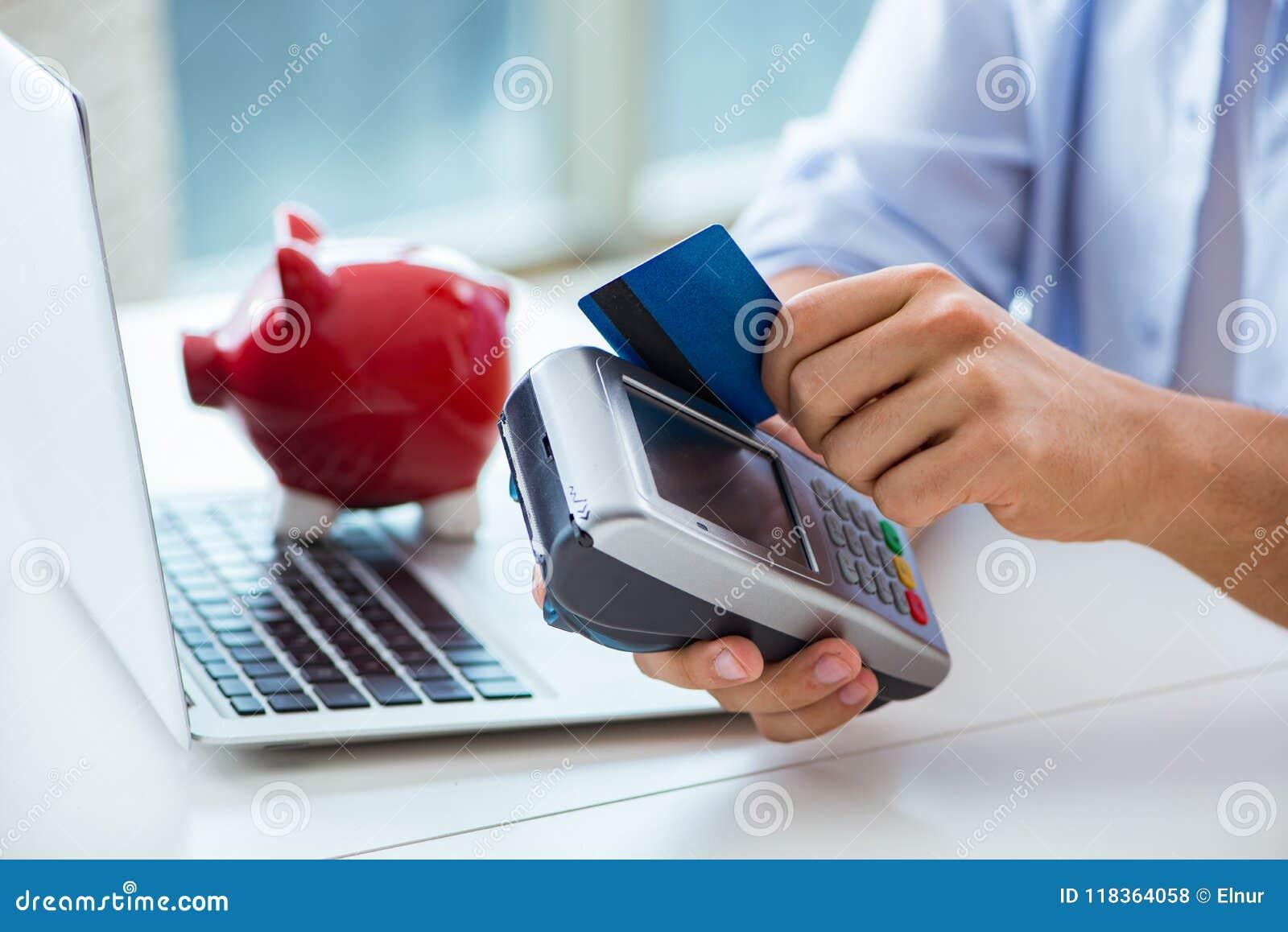 El hombre que procesa la transacción de la tarjeta de crédito con el terminal de la posición