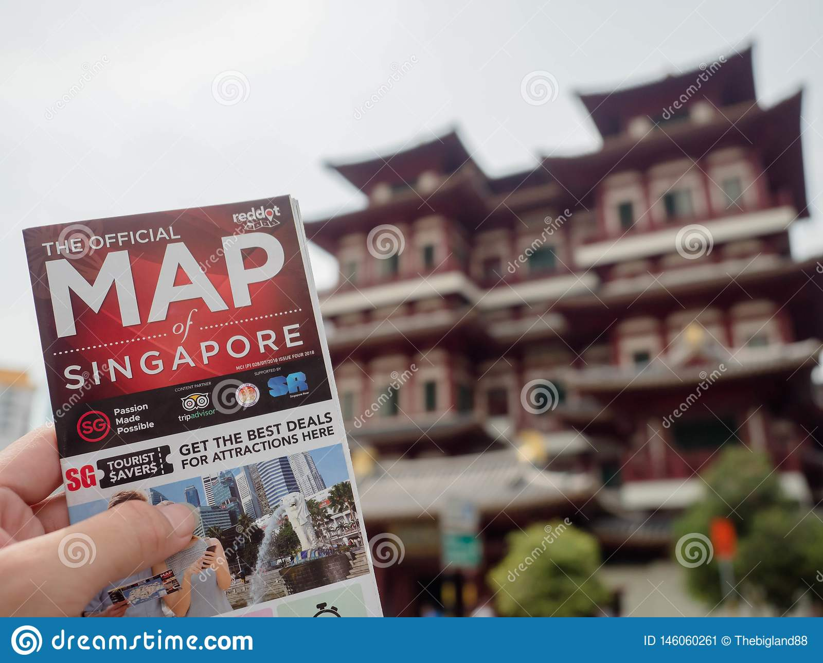 El hombre que sostiene un mapa de Singapur la parte posterior es templo de la reliquia de Buda Toothe en Chinatown Singapur