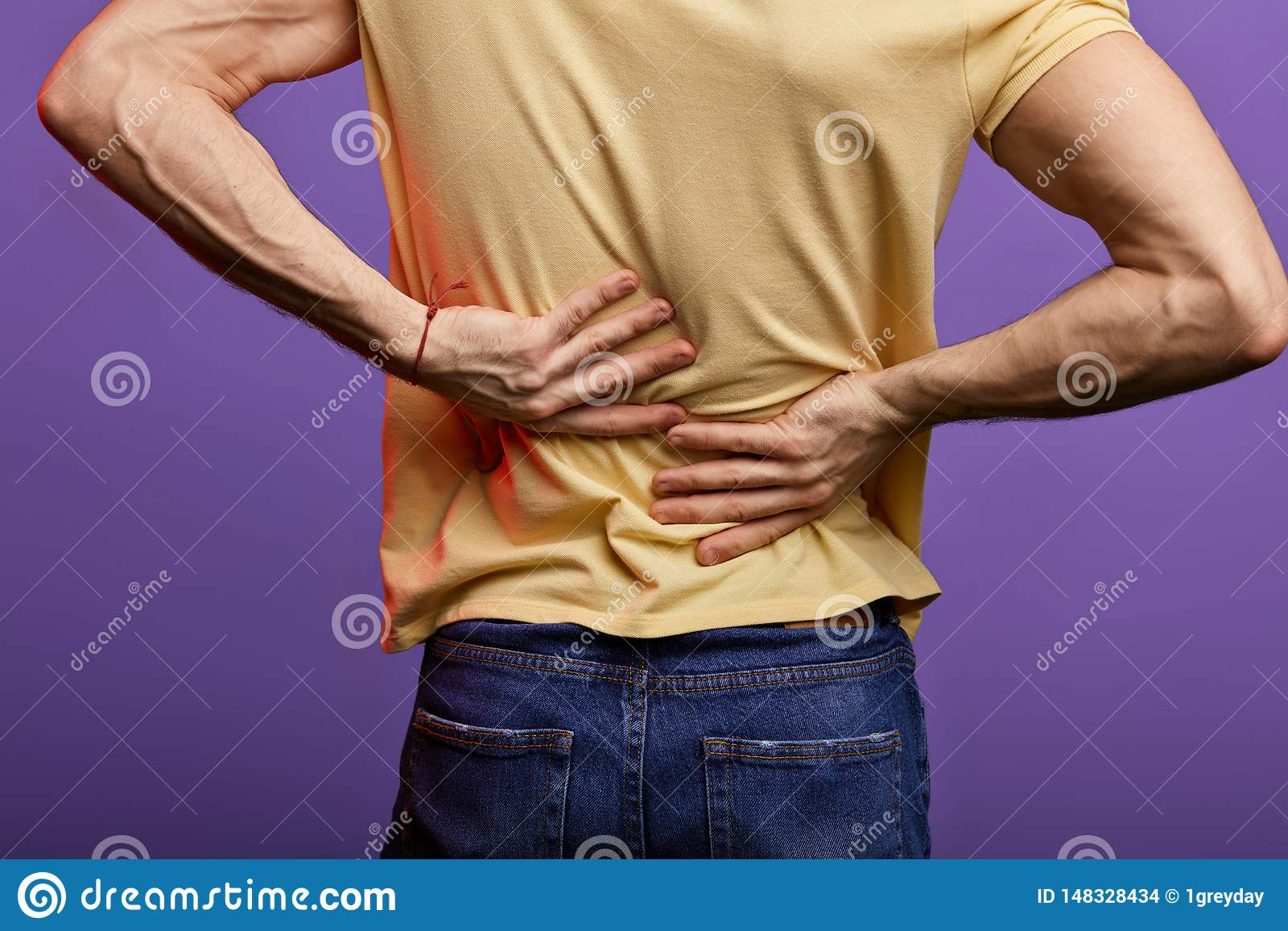 El hombre que toca el suyo detr?s, individuo tiene peoblems del disco en su parte posterior