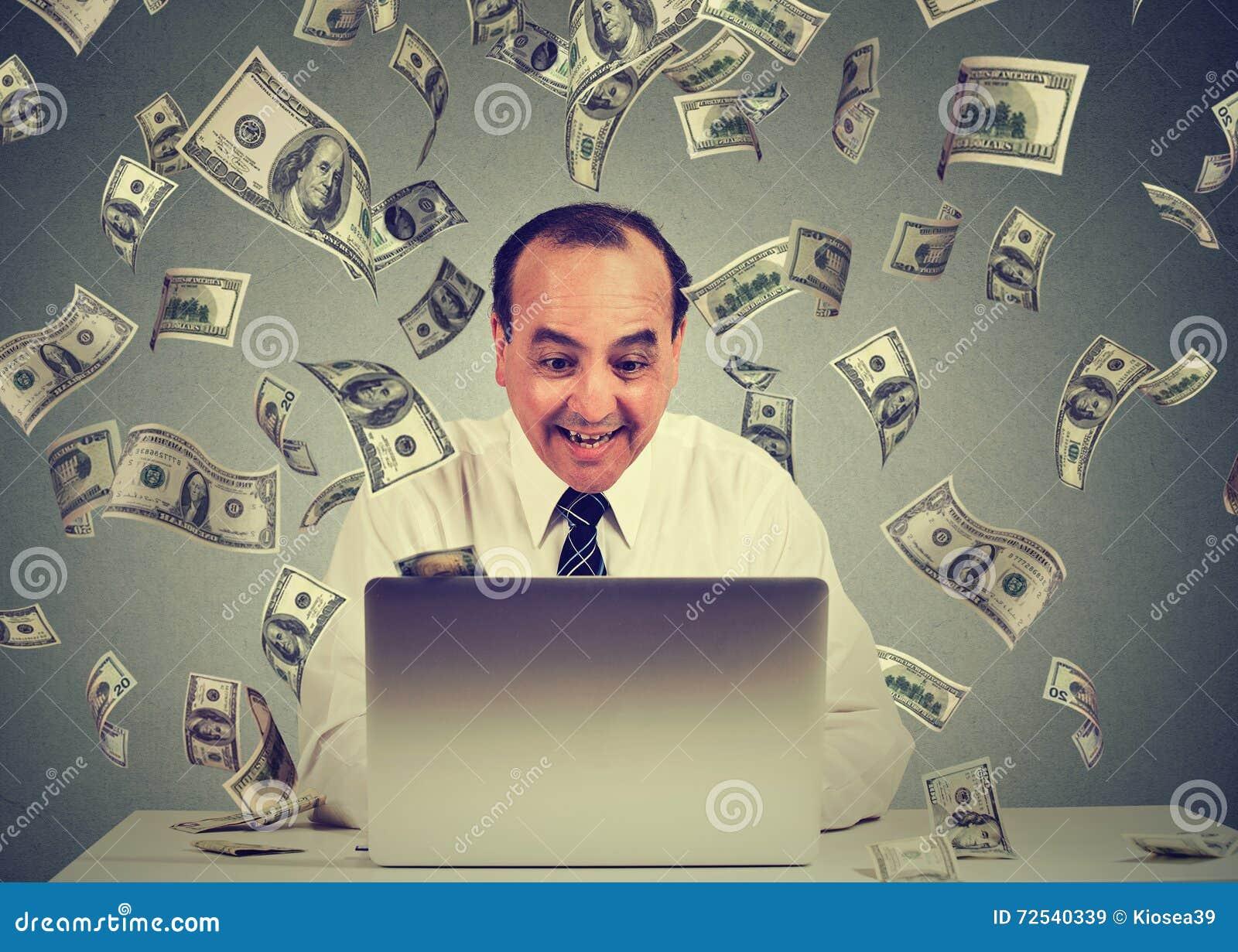 El hombre que usa el ordenador portátil que construye el negocio en línea que hace billetes de dólar del dinero cobra caer abajo