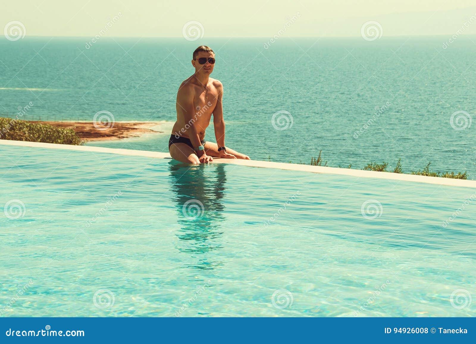 El hombre rico acertado que se relaja en piscina del infinito y disfruta de vacaciones Centro turístico de balneario Forma de vid