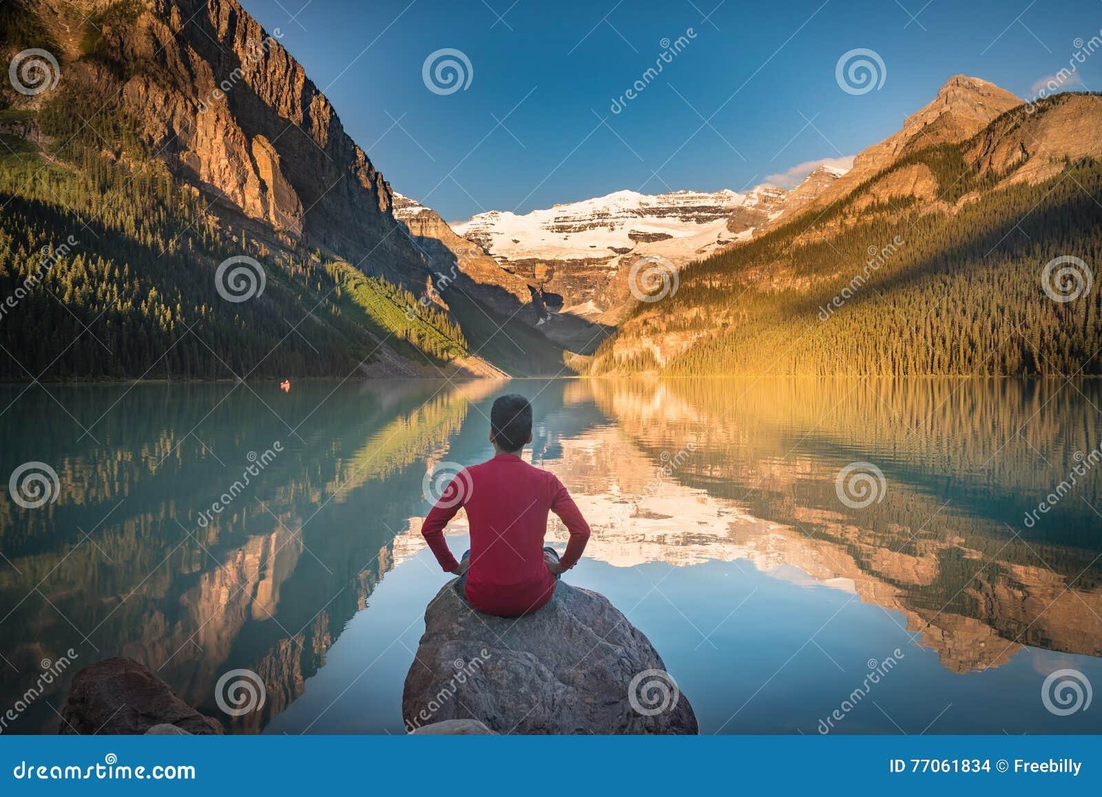 El hombre se sienta en roca que mira las reflexiones de Lake Louise
