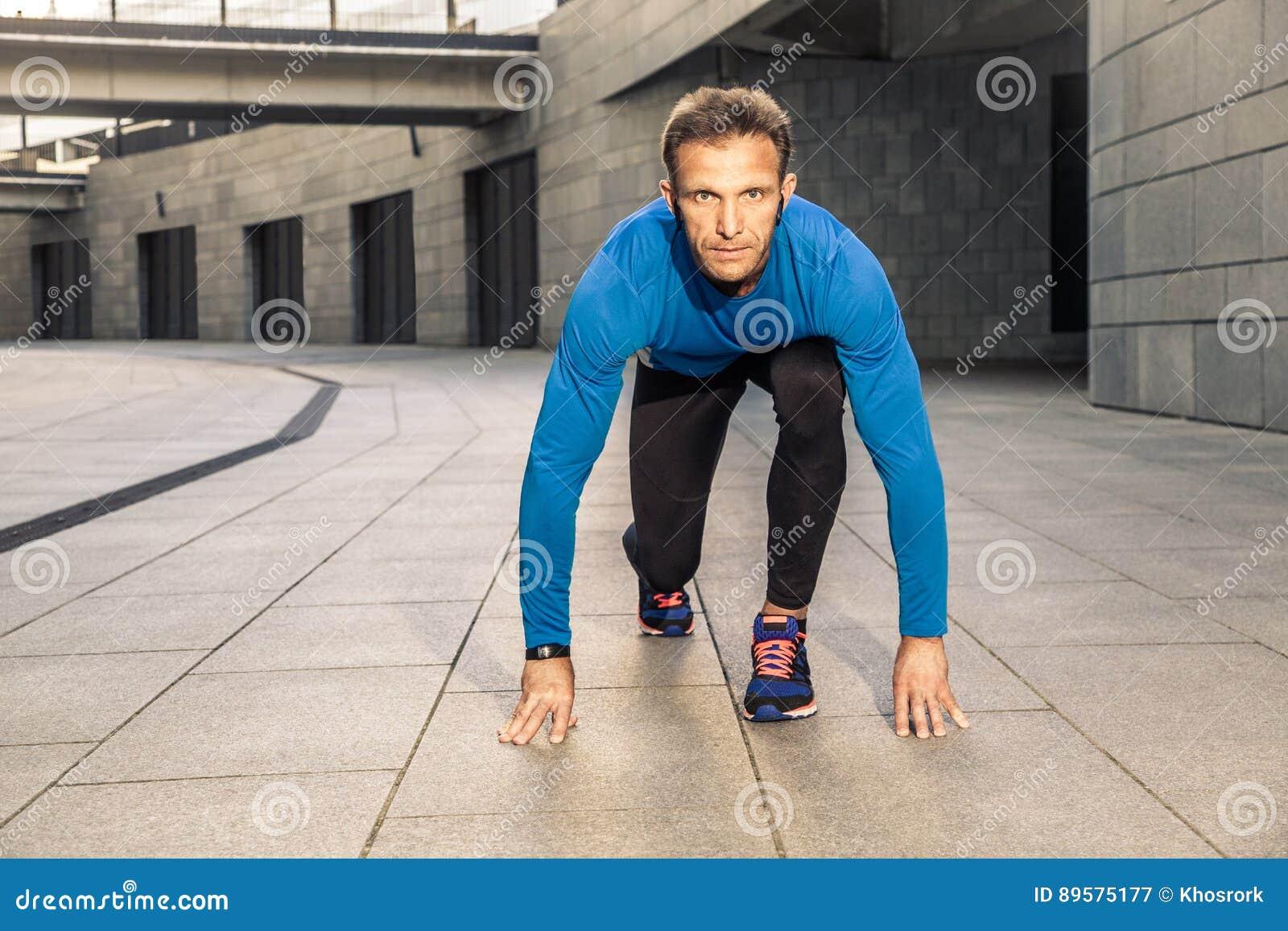 El hombre serio envejecido centro hermoso en los deportes uniforme y auriculares y perseguidor del negro azul de la aptitud está