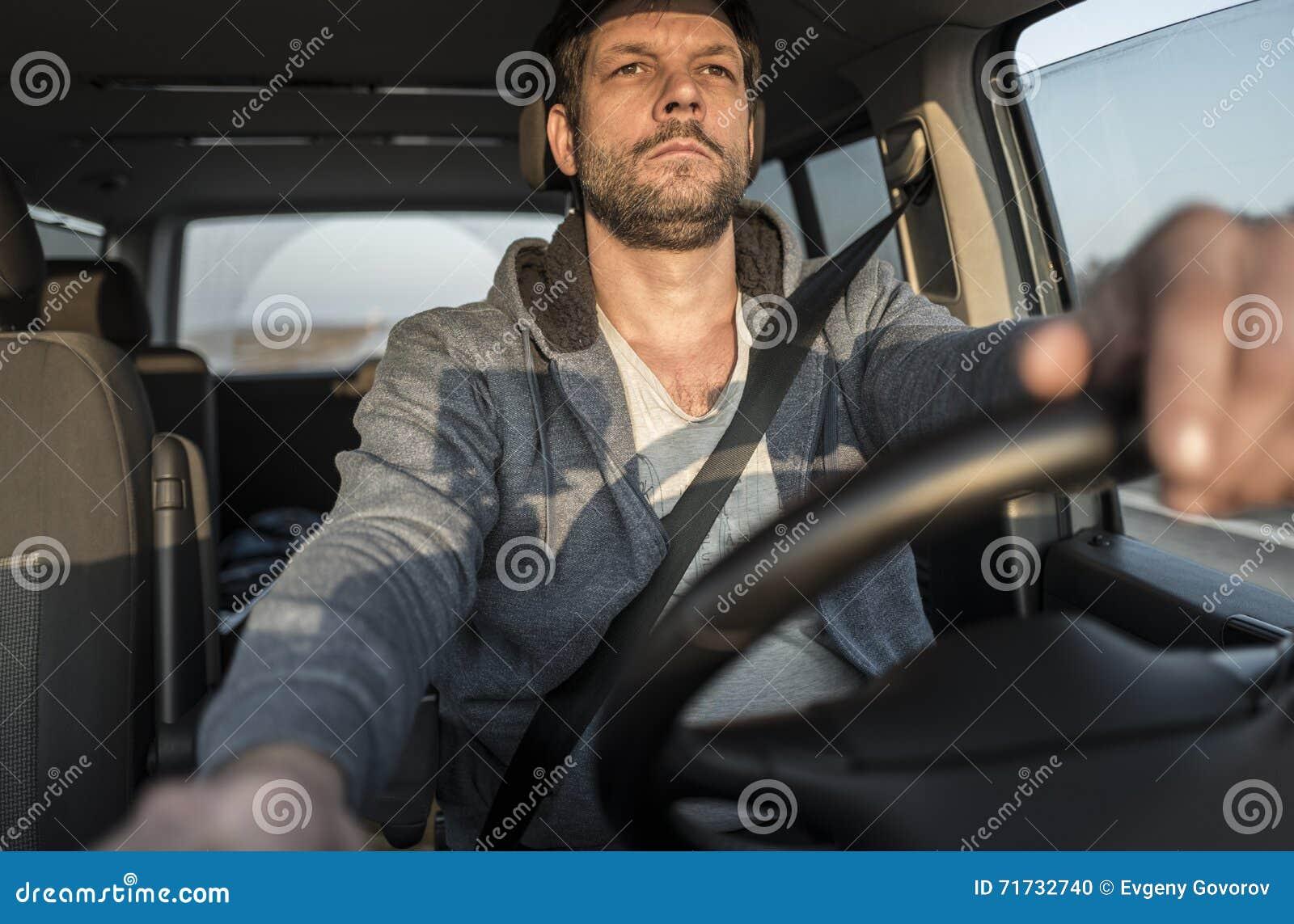 El hombre sin afeitar cansado está conduciendo el coche