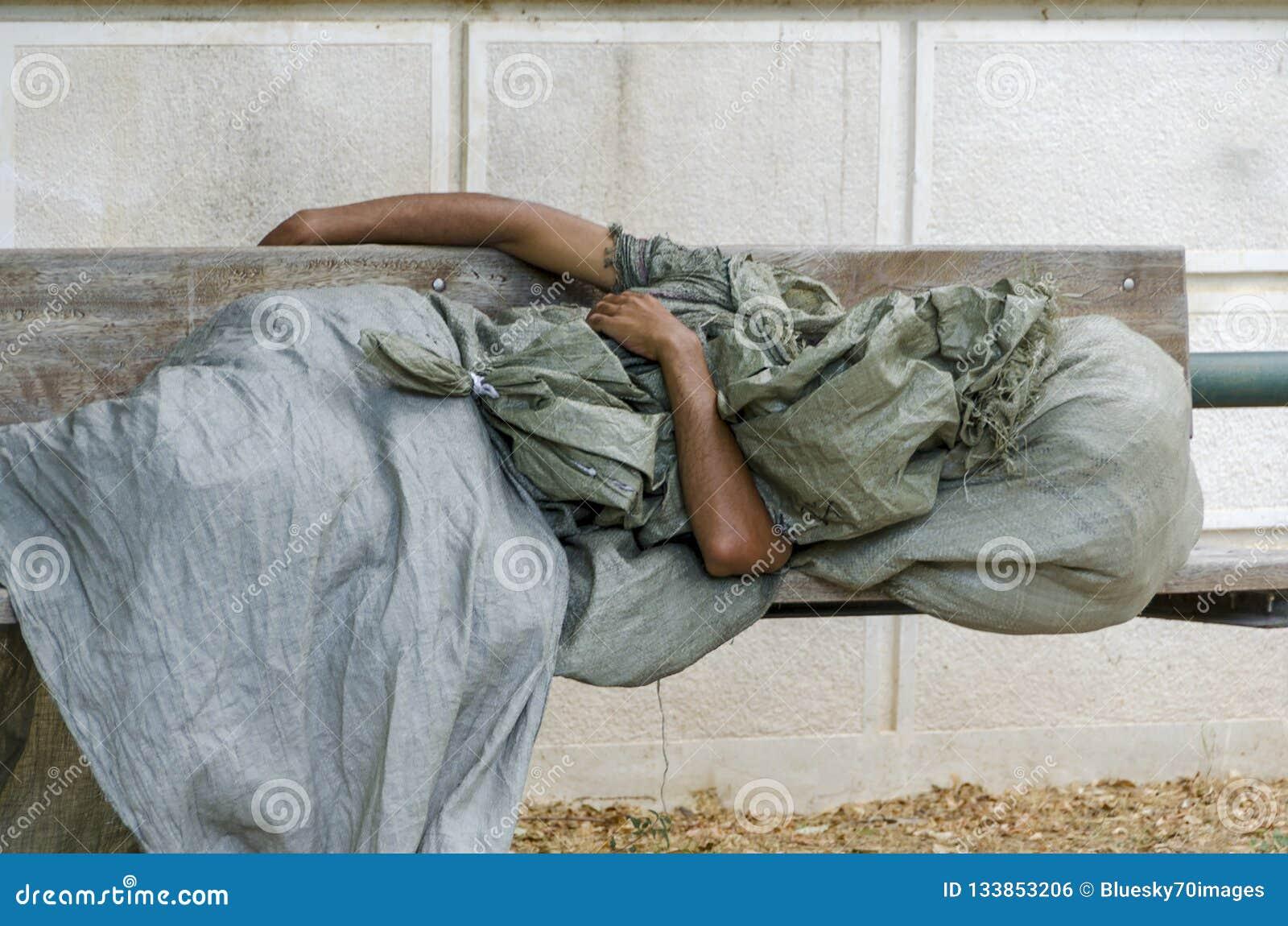El hombre sin hogar está durmiendo en un banco