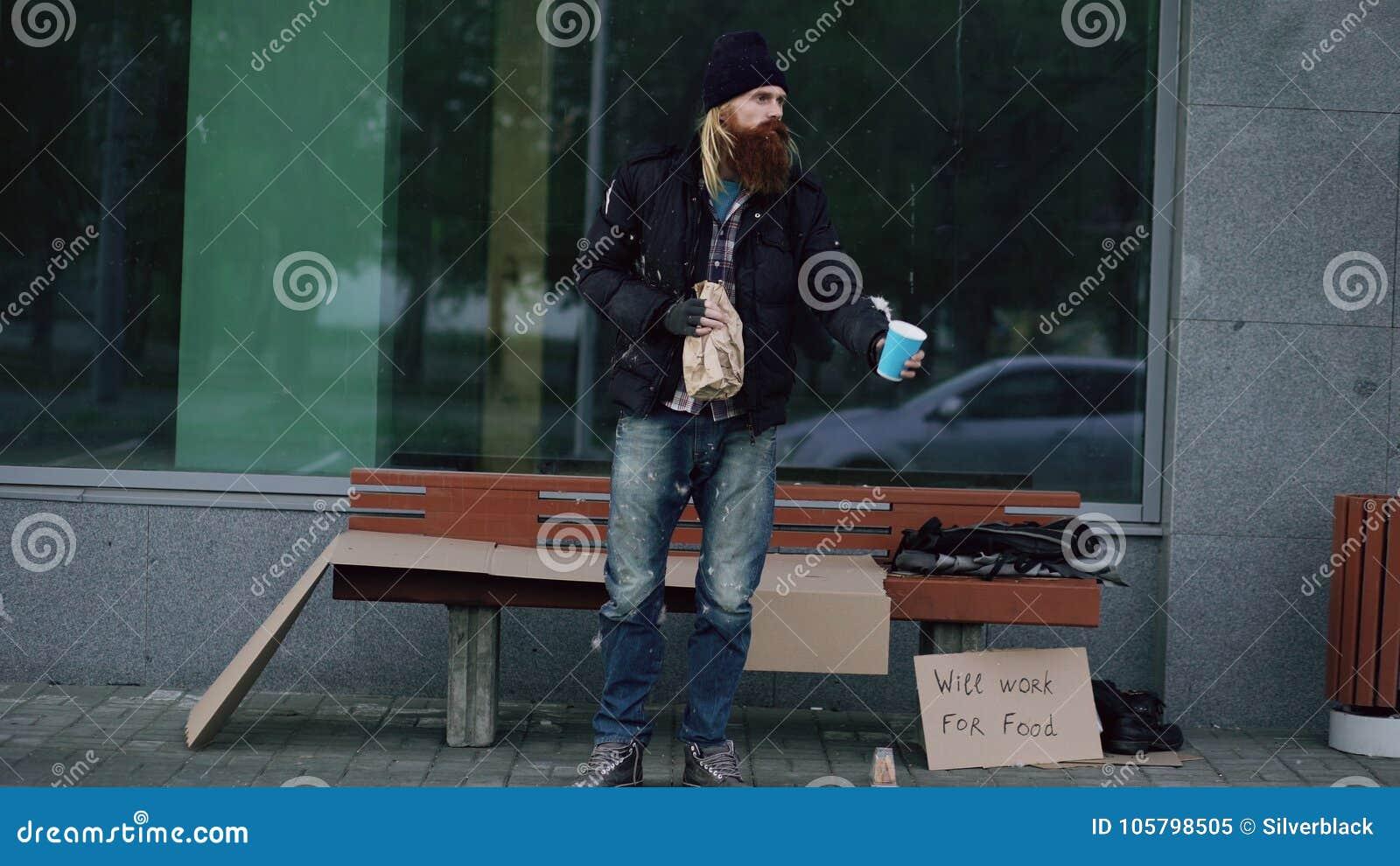 El hombre sin hogar muy borracho con la muestra de la cartulina y del alcohol pide dinero mientras que coloca el banco cercano en