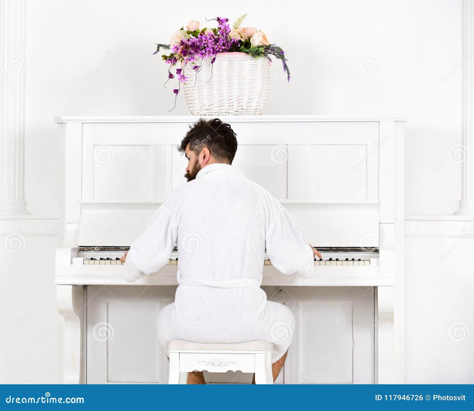 El hombre soñoliento en albornoz se sienta delante del instrumento musical del piano en el interior blanco en el fondo, vista pos