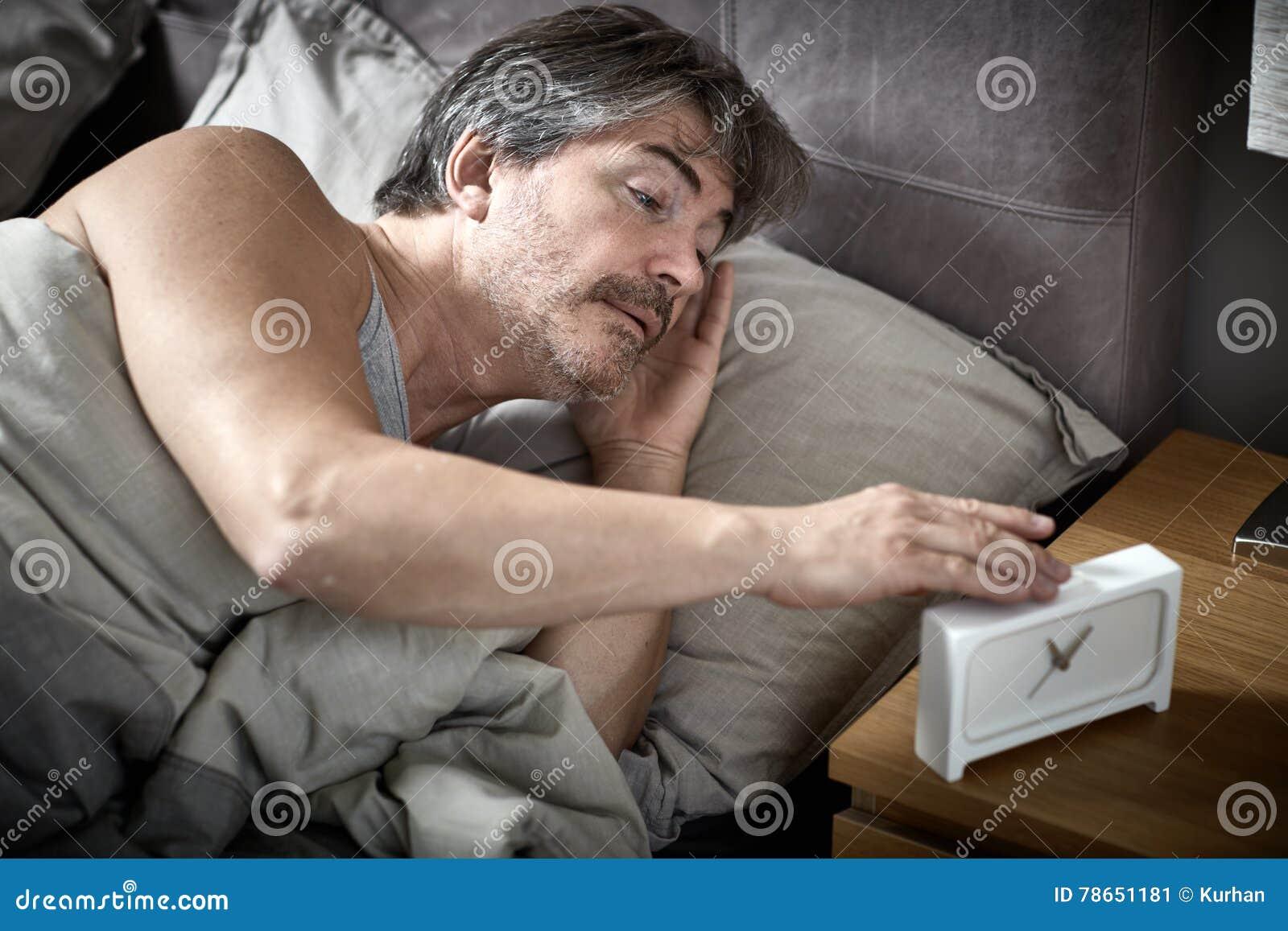 El hombre soñoliento en cama despierta