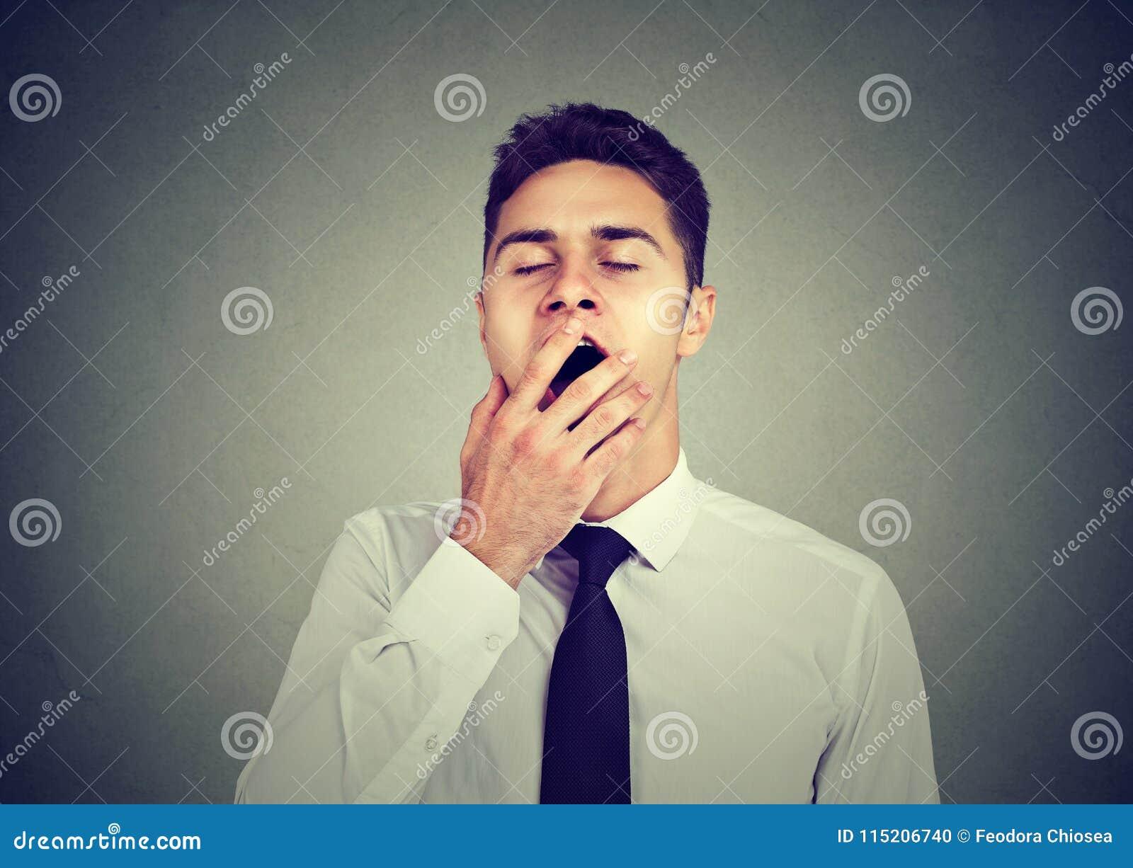 El hombre soñoliento que bosteza con entrega la boca