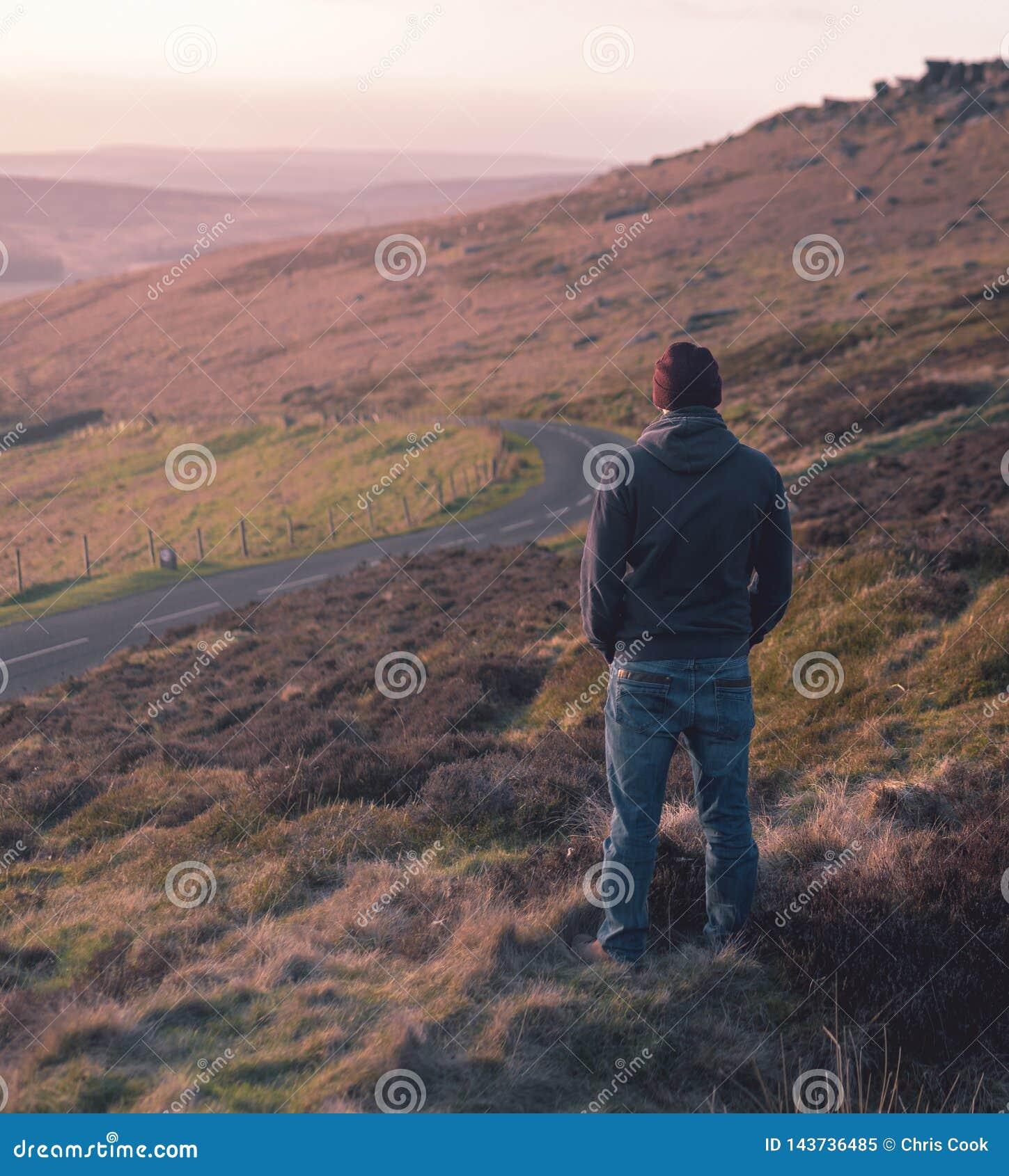 El hombre solitario mira fijamente hacia fuera sobre prado durante puesta del sol