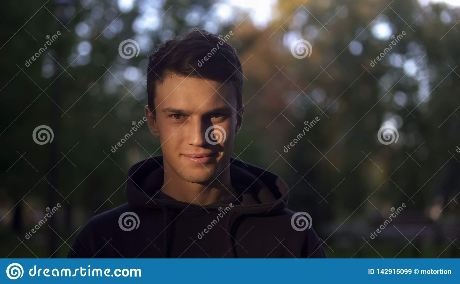 El hombre sonriente amistoso que mira la cámara en parque, alista para los cambios positivos de la vida