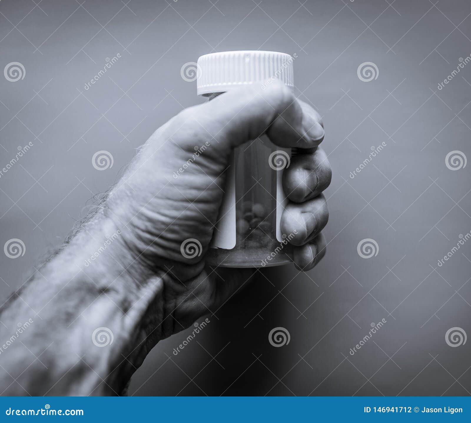 El hombre sostiene la botella pl?stica de p?ldoras de la prescripci?n Concepto de la atenci?n sanitaria o del apego