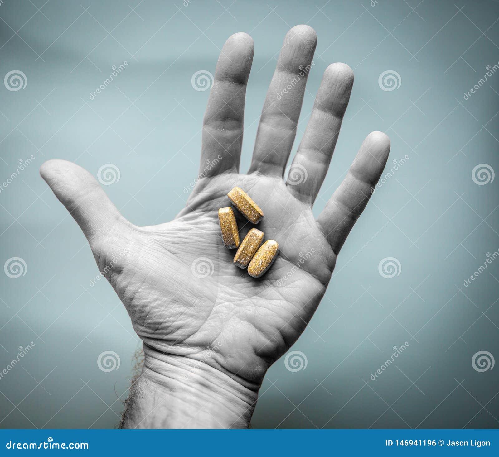 El hombre sostiene las vitaminas o las p?ldoras de la prescripci?n en la palma de la mano Concepto de la atenci?n sanitaria o del