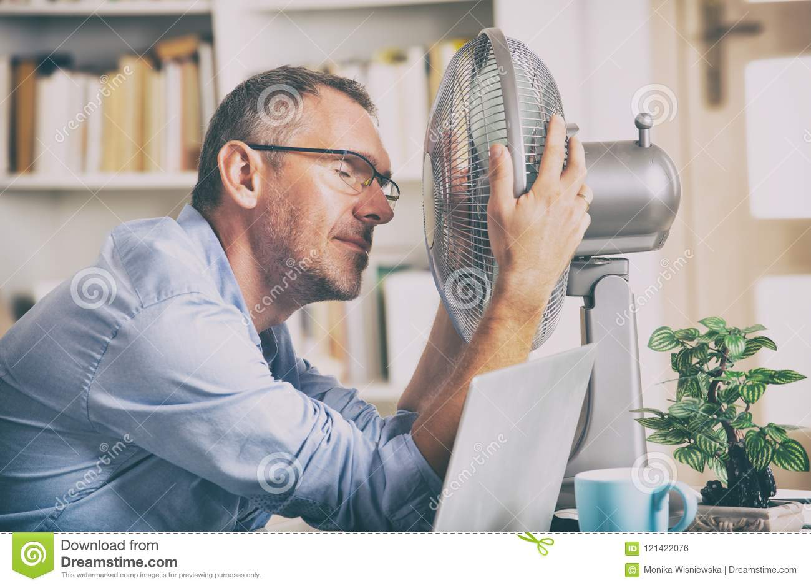 El hombre sufre de calor en la oficina o en casa
