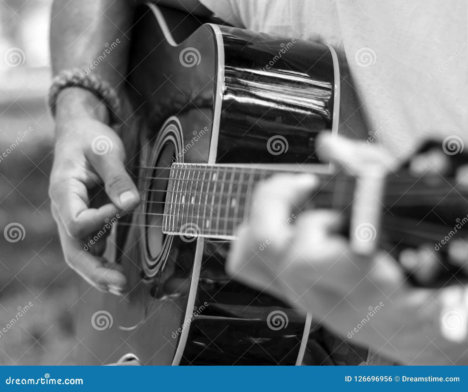 El hombre toca la guitarra en tonos blancos y negros